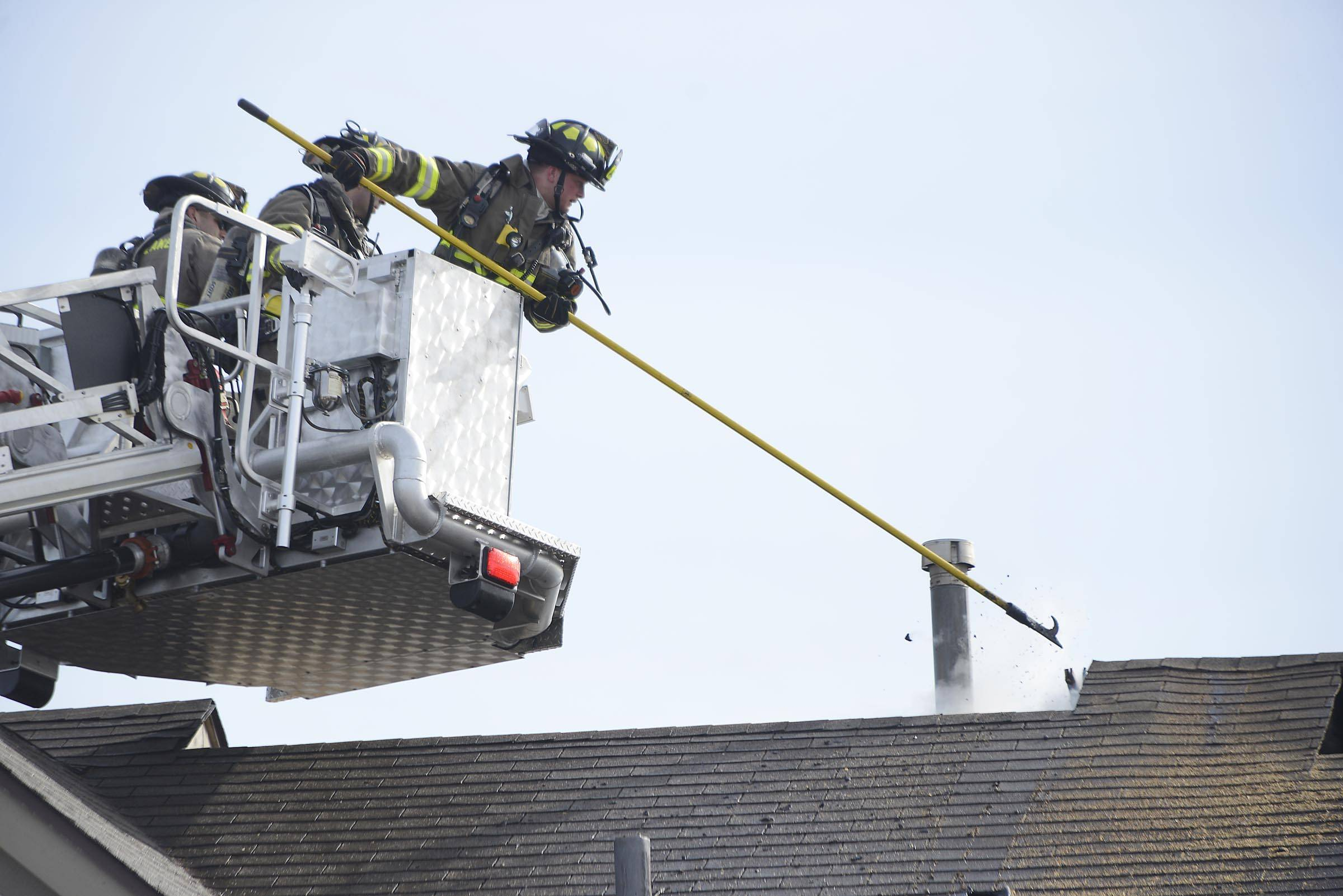 Firefighters open the roof of a condominium on the 1600 block of Carlemont Drive in Crystal Lake as a fire spreads through the roof Monday afternoon.