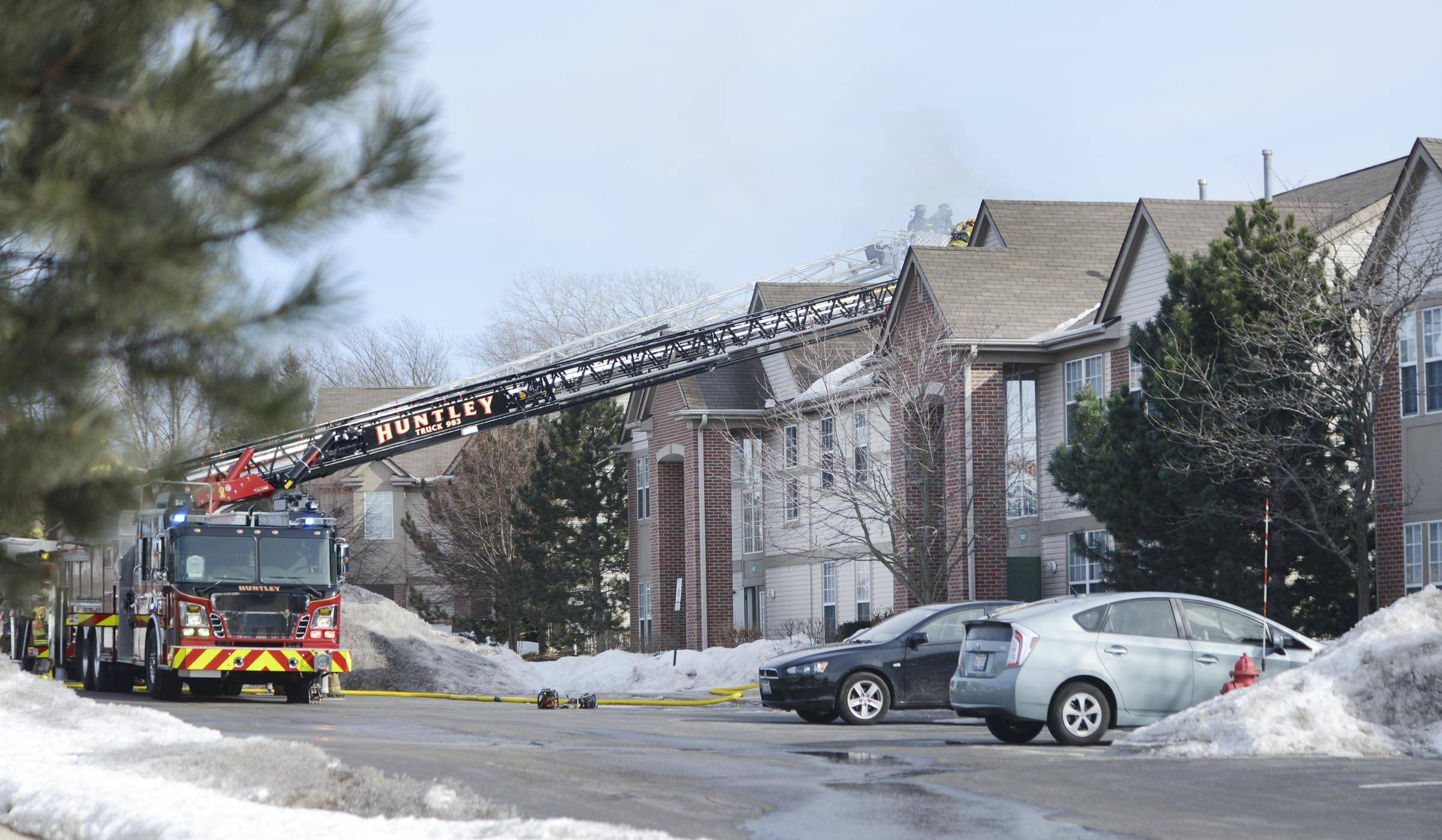 Firefighters open the roof of a condominium at 1623 Carlemont Drive in Crystal Lake as a fire spreads through the roof Monday afternoon.