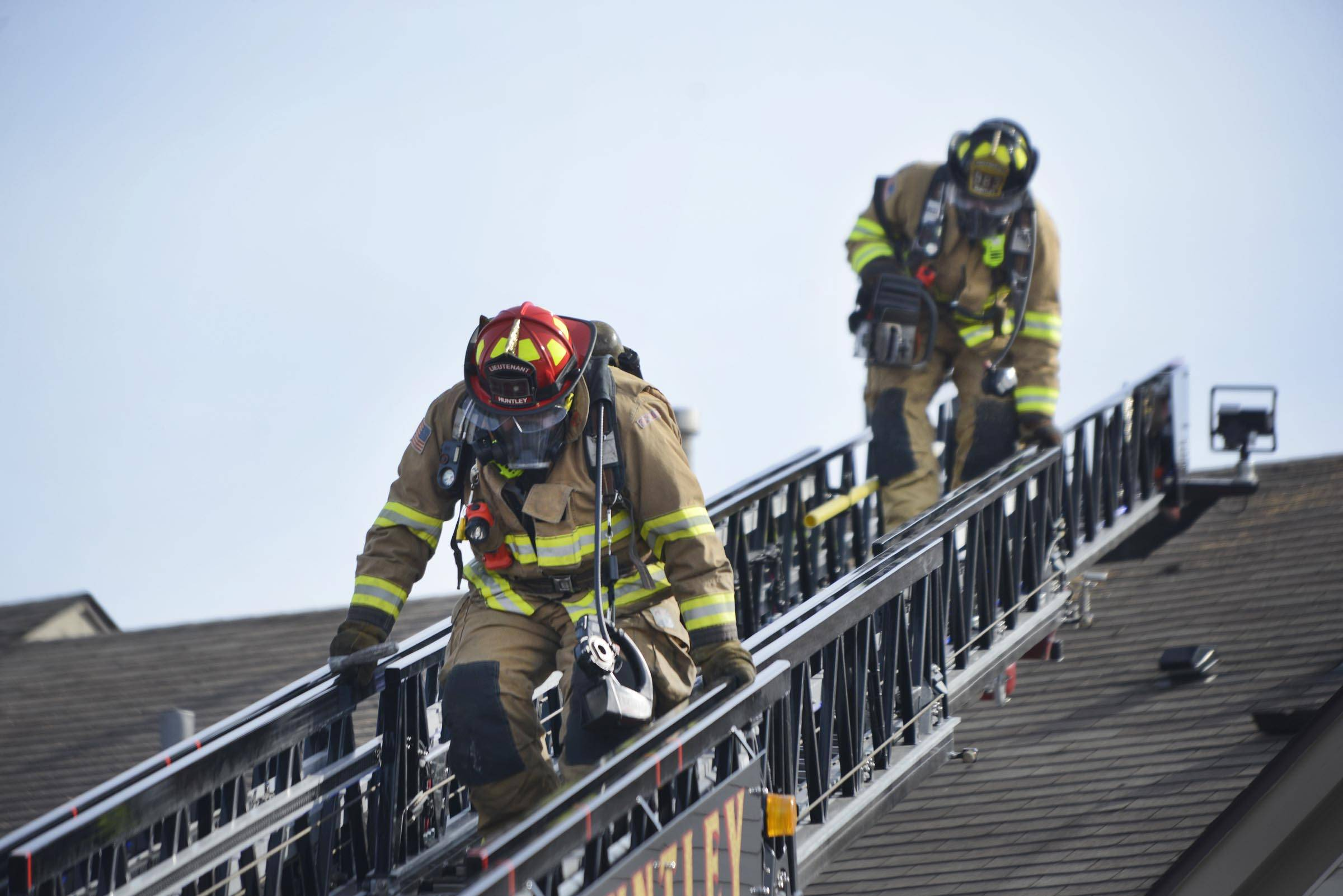 Firefighters come down from a ladder truck set up at 1623 Carlemont Drive in Crystal Lake as a fire spreads through the roof Monday afternoon.