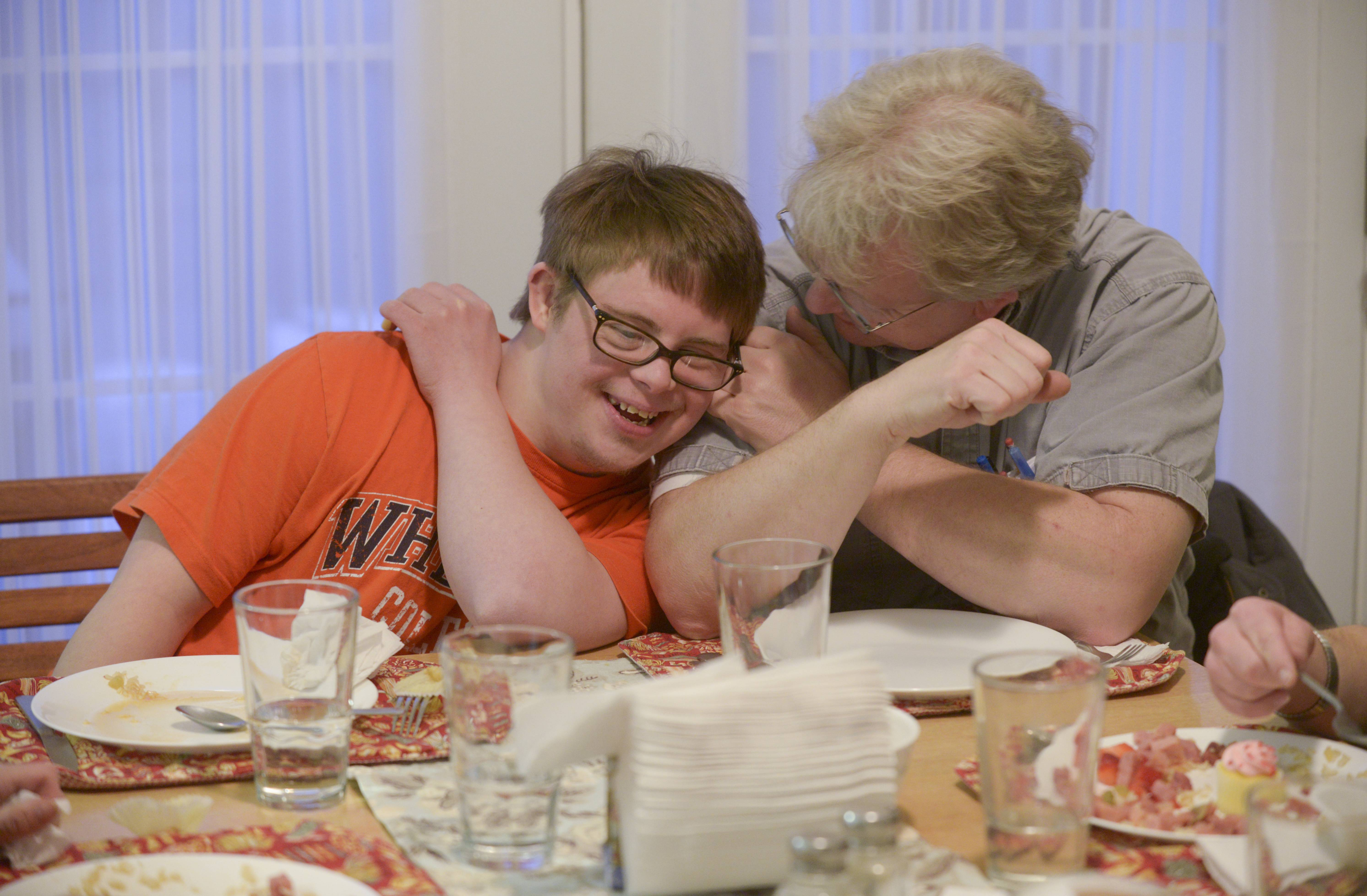 Washington House resident David Brinker, left, and staff member Trace Nelson share a moment during dinner.