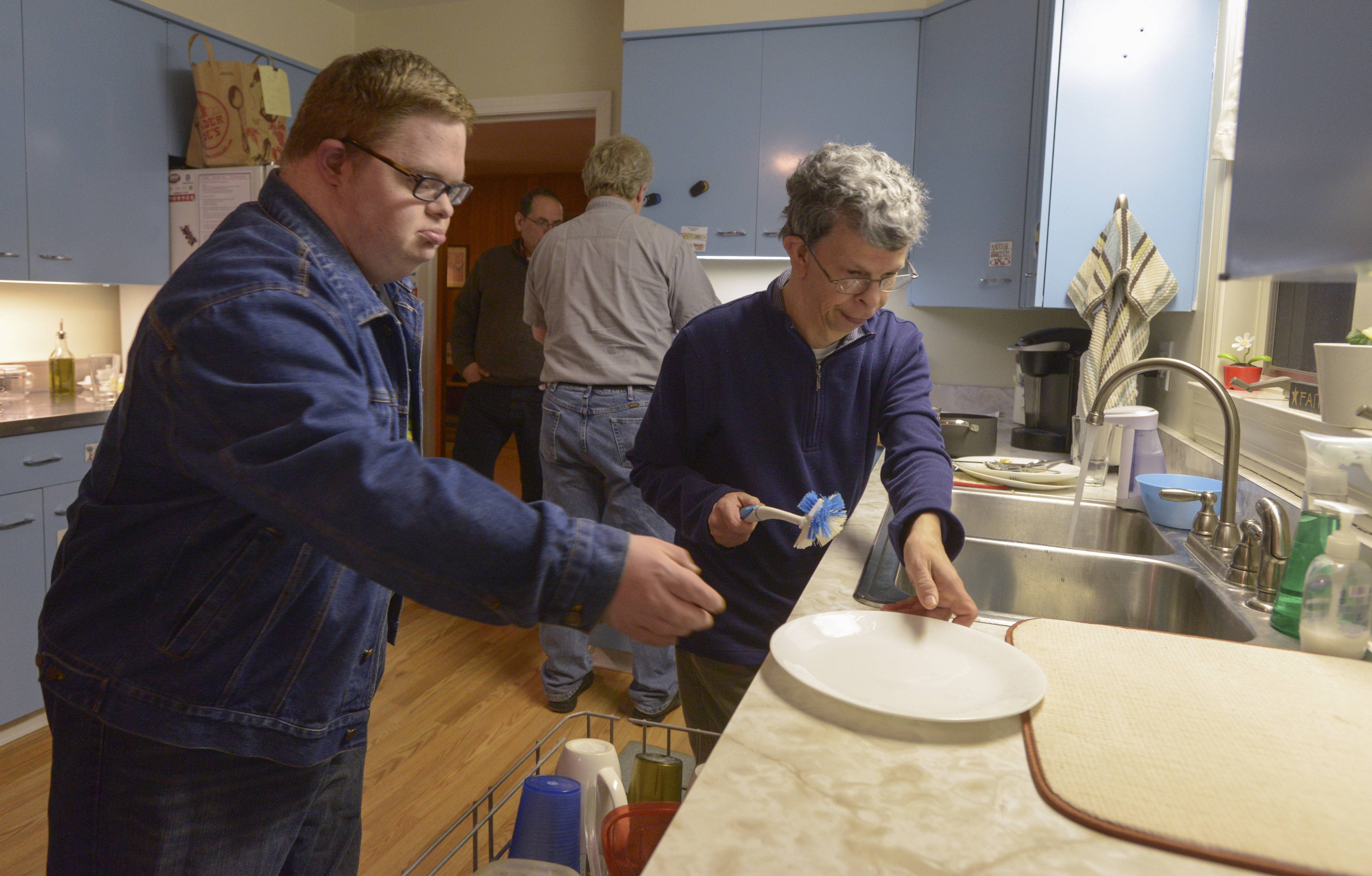 After dinner Washington House residents Ian Kenneally, left, and Gary Brunette clean the dishes as part of their nightly chores.