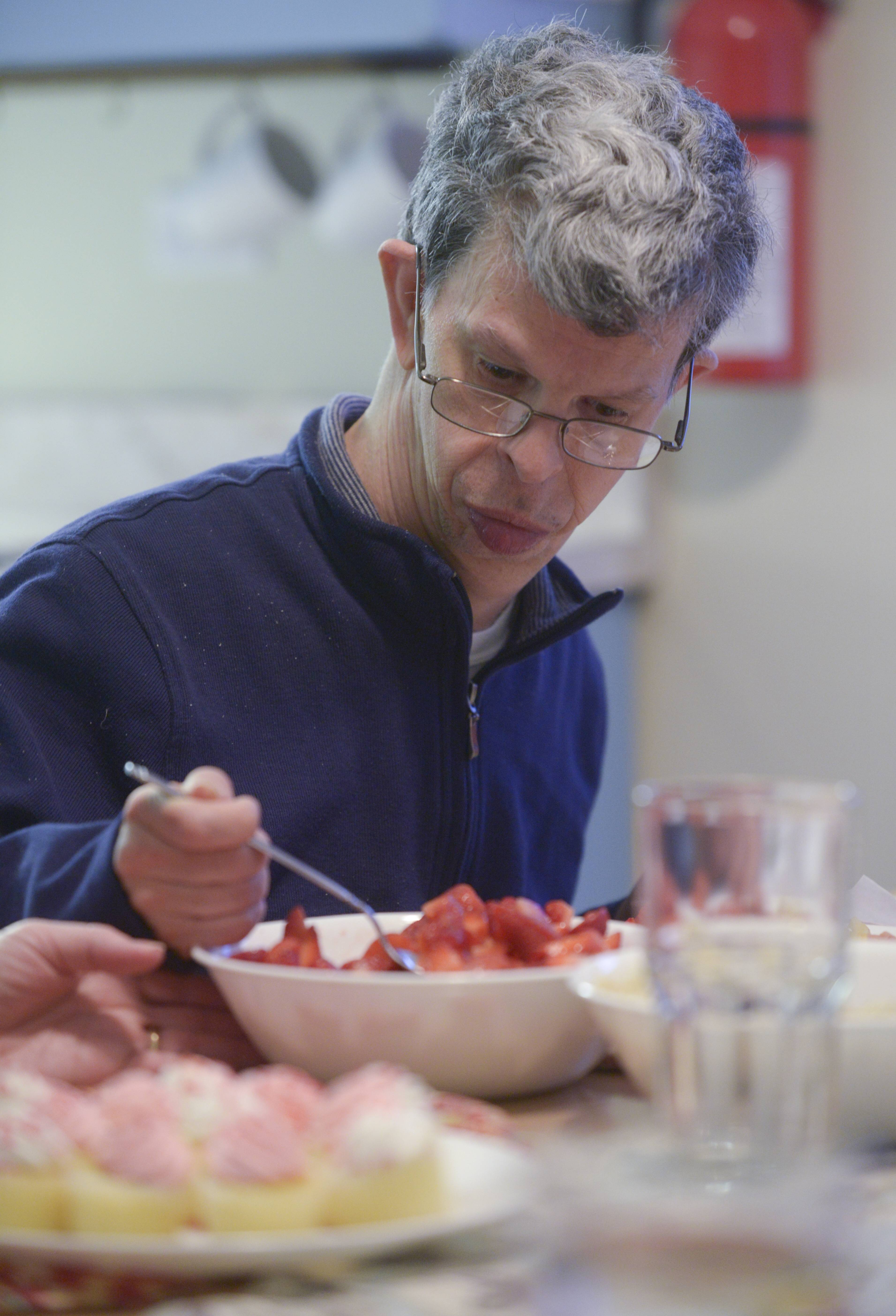 Gary Brunette, the designated cook for the week at Washington House, dishes up some strawberries as part of the meal he has prepared.