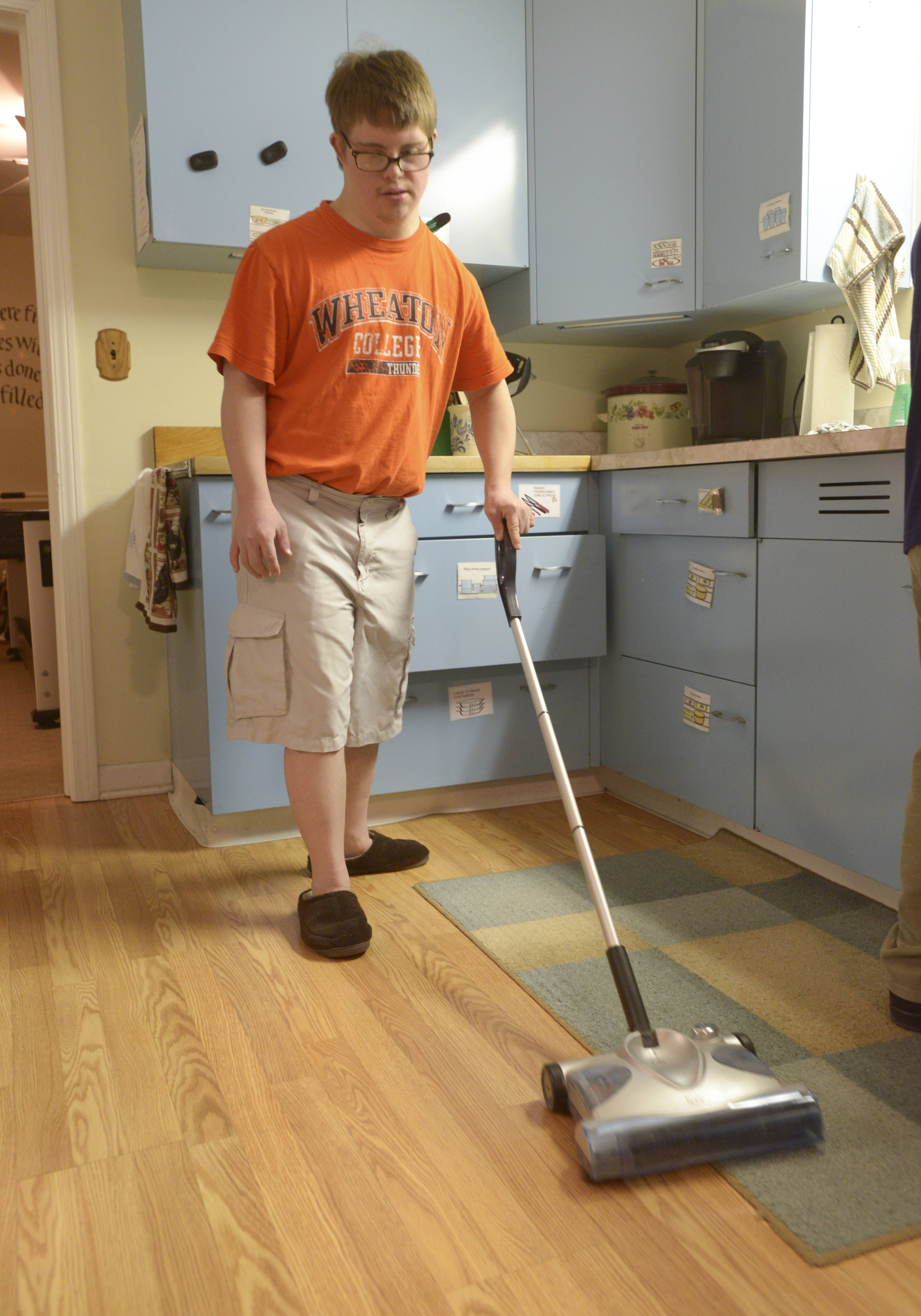 Washington House resident David Brinker cleans the floor after dinner. All the residents have weekly and monthly chores.