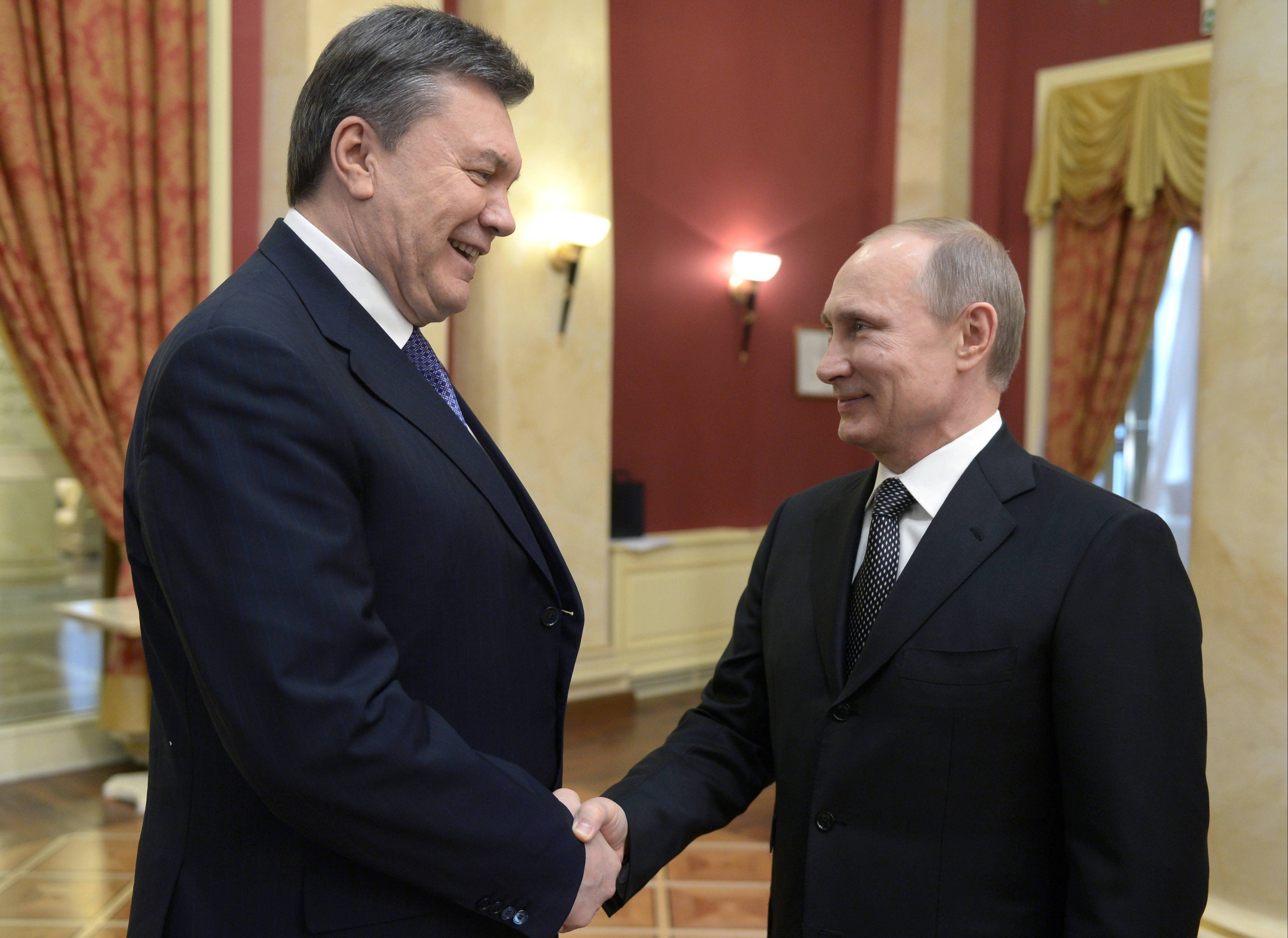 Russian President Vladimir Putin, right, is seen with Ukrainian President Viktor Yanukovych at the Olympic reception hosted by the Russian President in Sochi, Russia, Feb. 7. Now Yanukovych is on the run, and Putin is faced with a difficult question of how to react to events in Ukraine.