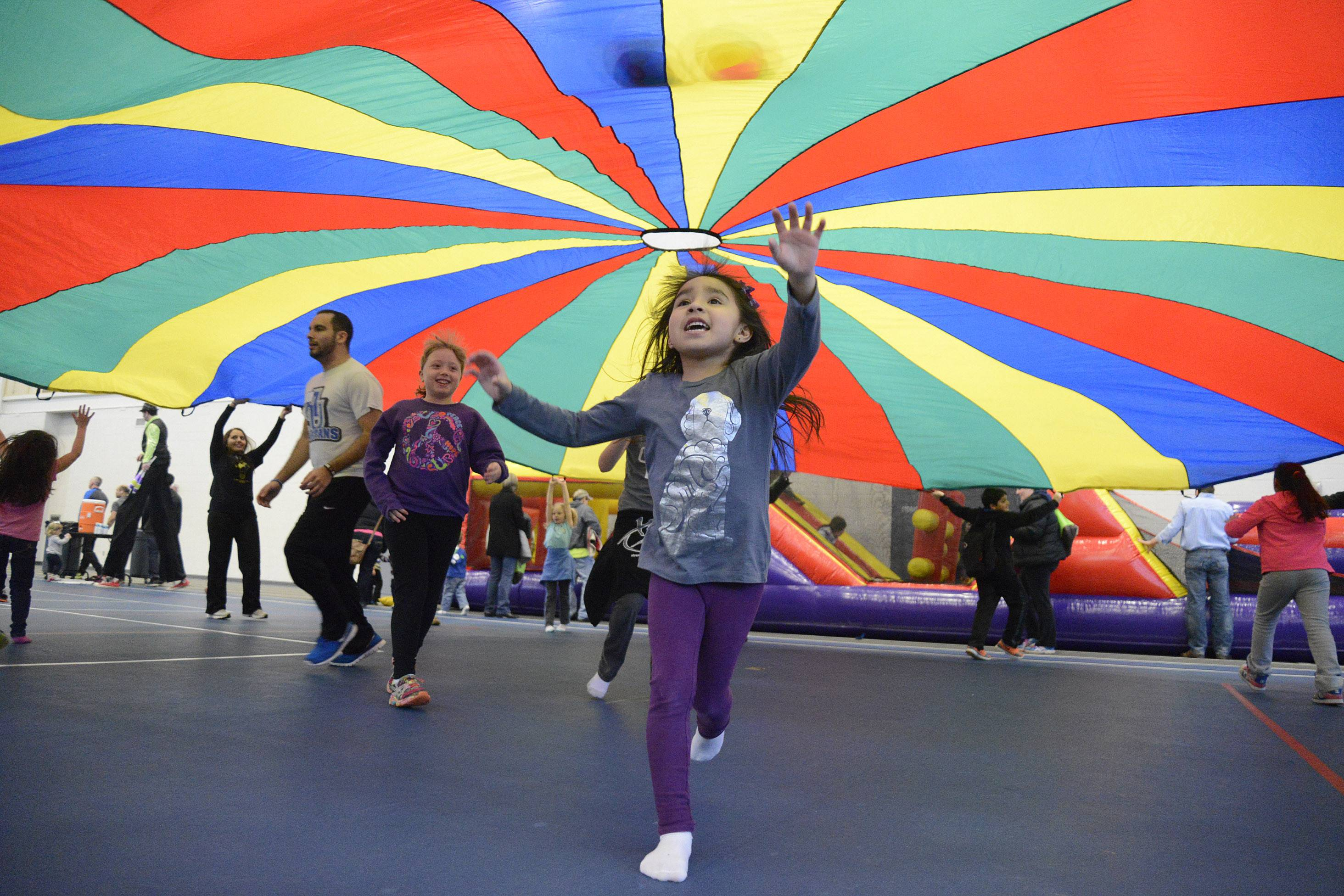 Alexa Bejarano, 5, of Aurora, runs to a yellow slice of color under the parachute activity at the annual Fitness Fun Fair for Kids at the Vaughn Athletic Center in Aurora on Saturday. The Bejarano family are members of the center and have been coming to the Fun Fair for the past three years.