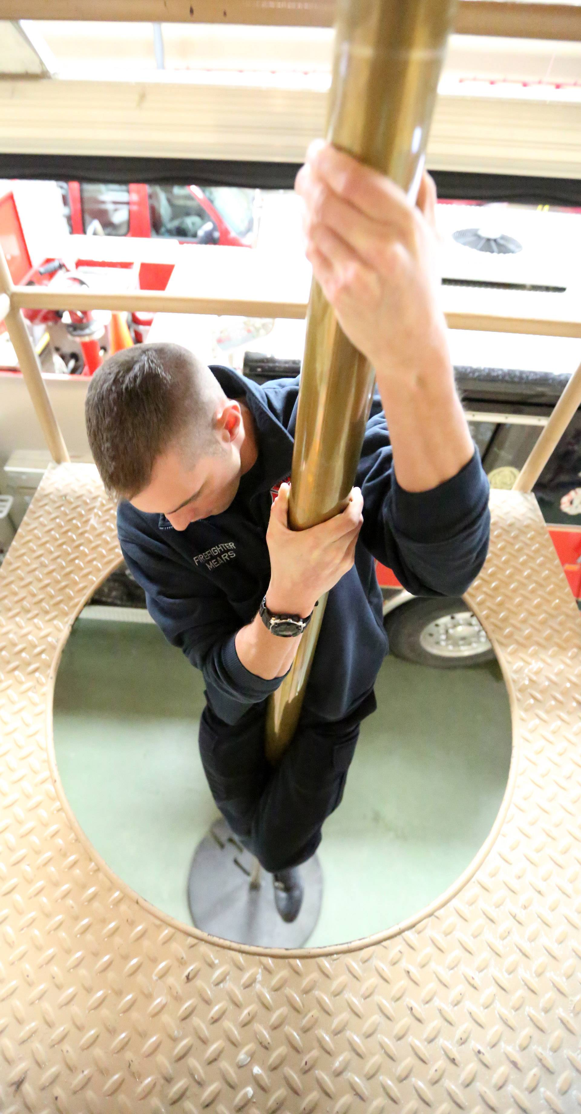 Streamwood firefighter/paramedic Brandon Mears simulates going down the Streamwood Fire Station No. 1's pole on Thursday in Streamwood. Mears said it's the only Streamwood station with a pole and the firefighters really use it. Their bunks are near the the top of the pole.