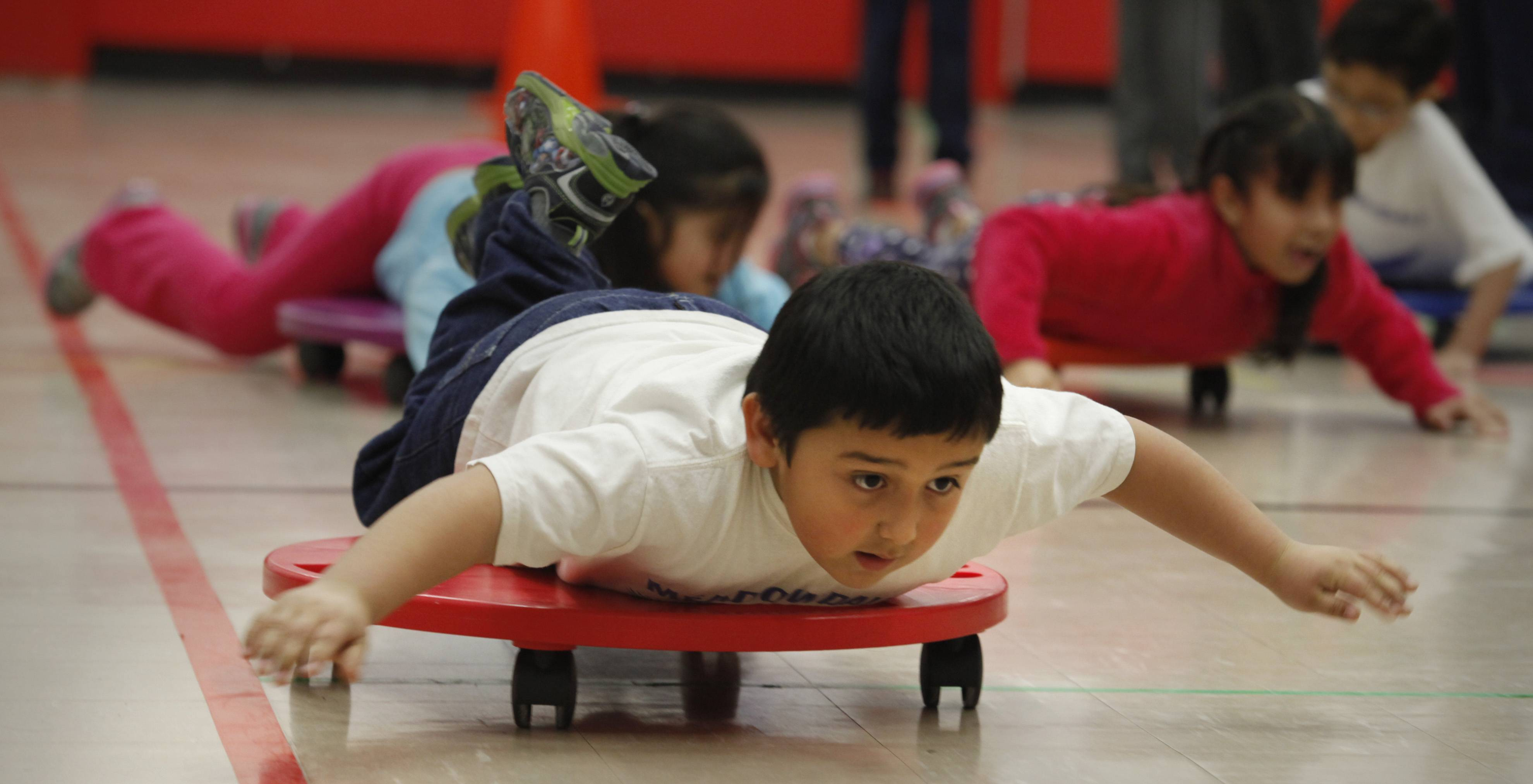 Meadowdale Elementary first-grader Juan Tinajeros sails across the floor on a wheeled scooter as he and his classmates try out their own version of the olympic skeleton event Friday in Carpentersville.