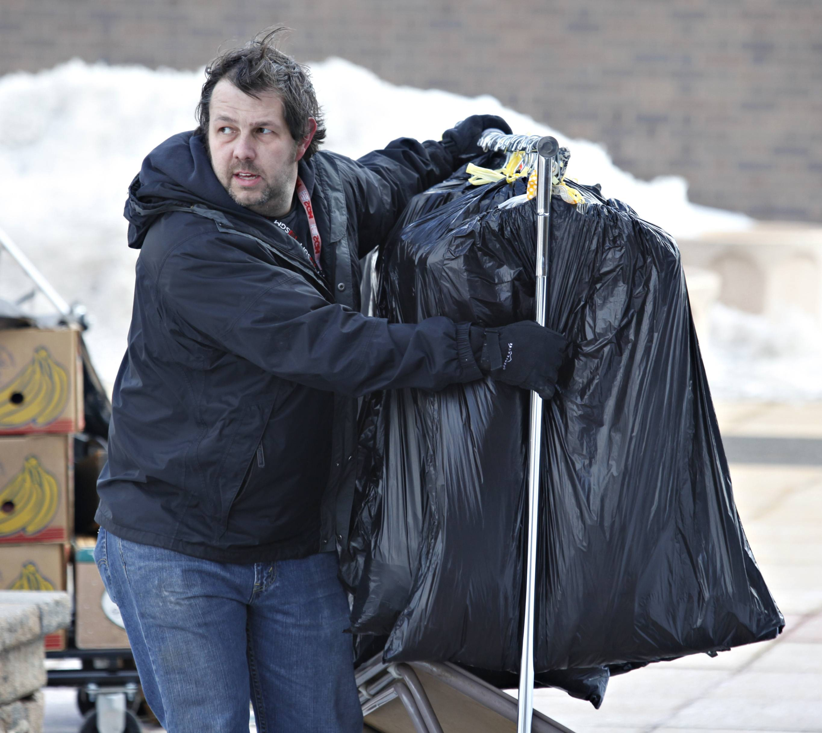Larkin High School faculty member Adam Baxter braces against the wind as he helps to porter racks of vintage clothing into the Hemmens Auditorium Friday afternoon in preparation for the Cat's Pajamas Chicagoland Vintage Clothing, Jewelry and Textile Show & Sale.