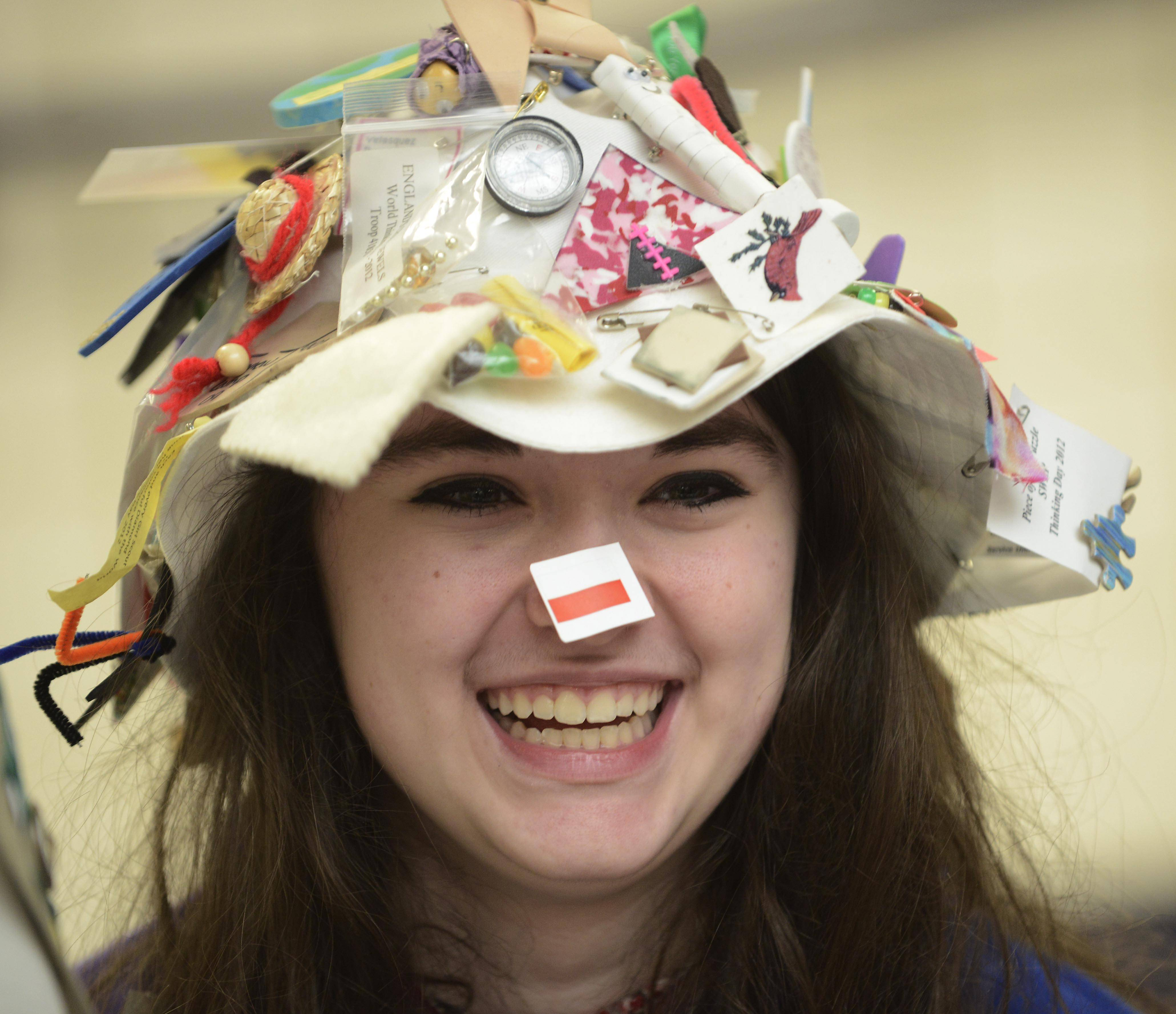"Kara White, 14, of Hoffman Estates, wears a SWAP hat, which displays items she has collected from each station during ""Thinking Day,"" an international festival of sisterhood in the Conant High School cafeteria Saturday morning."