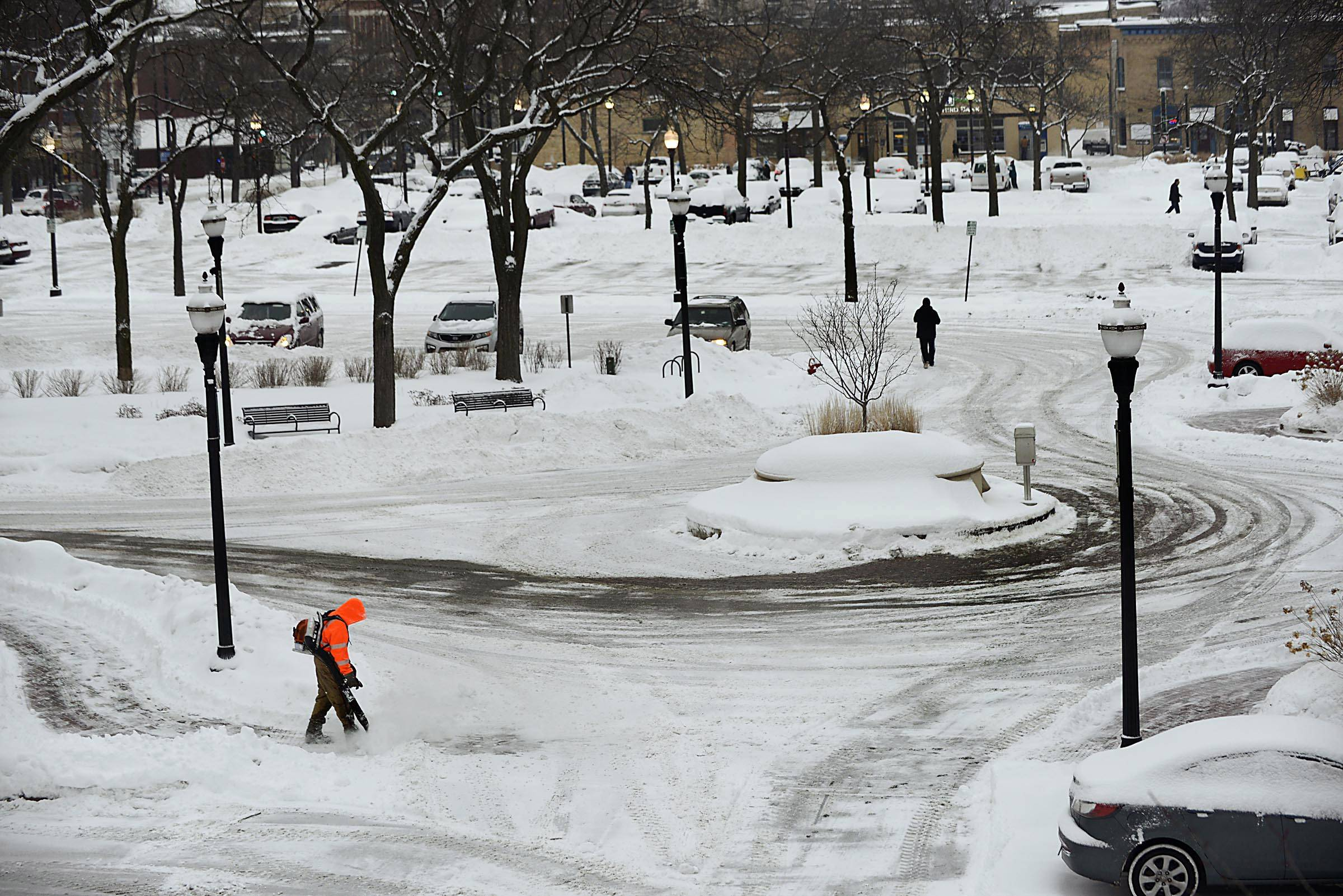 A worker uses a leaf blower to clear late afternoon snow from already-plowed sidewalks at Elgin City Hall Monday.