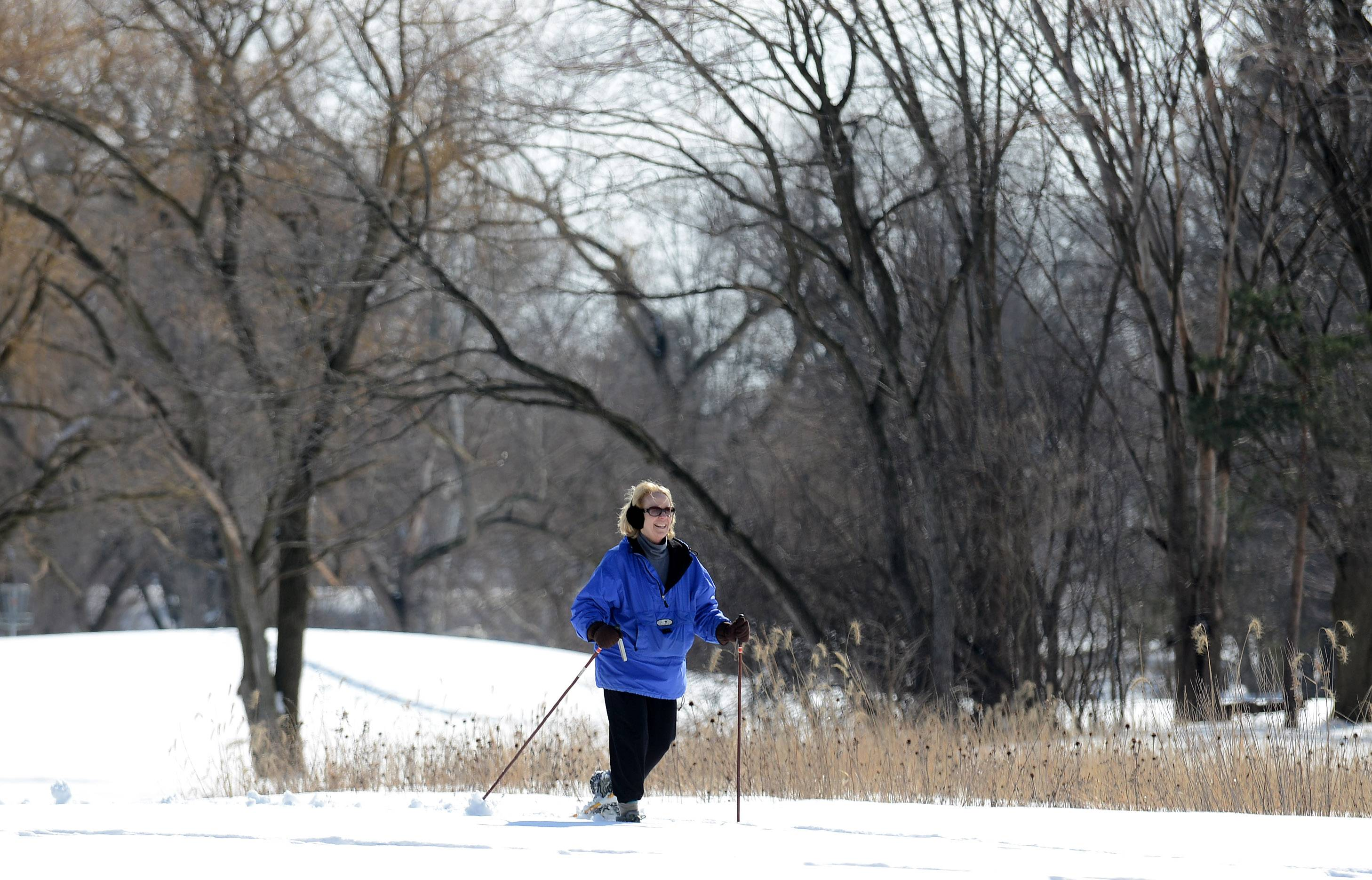 "Joyce Senters, of St. Charles, snow shoes through Wheeler Park in Geneva Tuesday. Tuesday's relatively balmy high in the 40s had Senters all smiles as she trekked through the snow. ""It's so beautiful out with the fresh snow and the blue skies,"" she said. ""What's not to smile about?"""