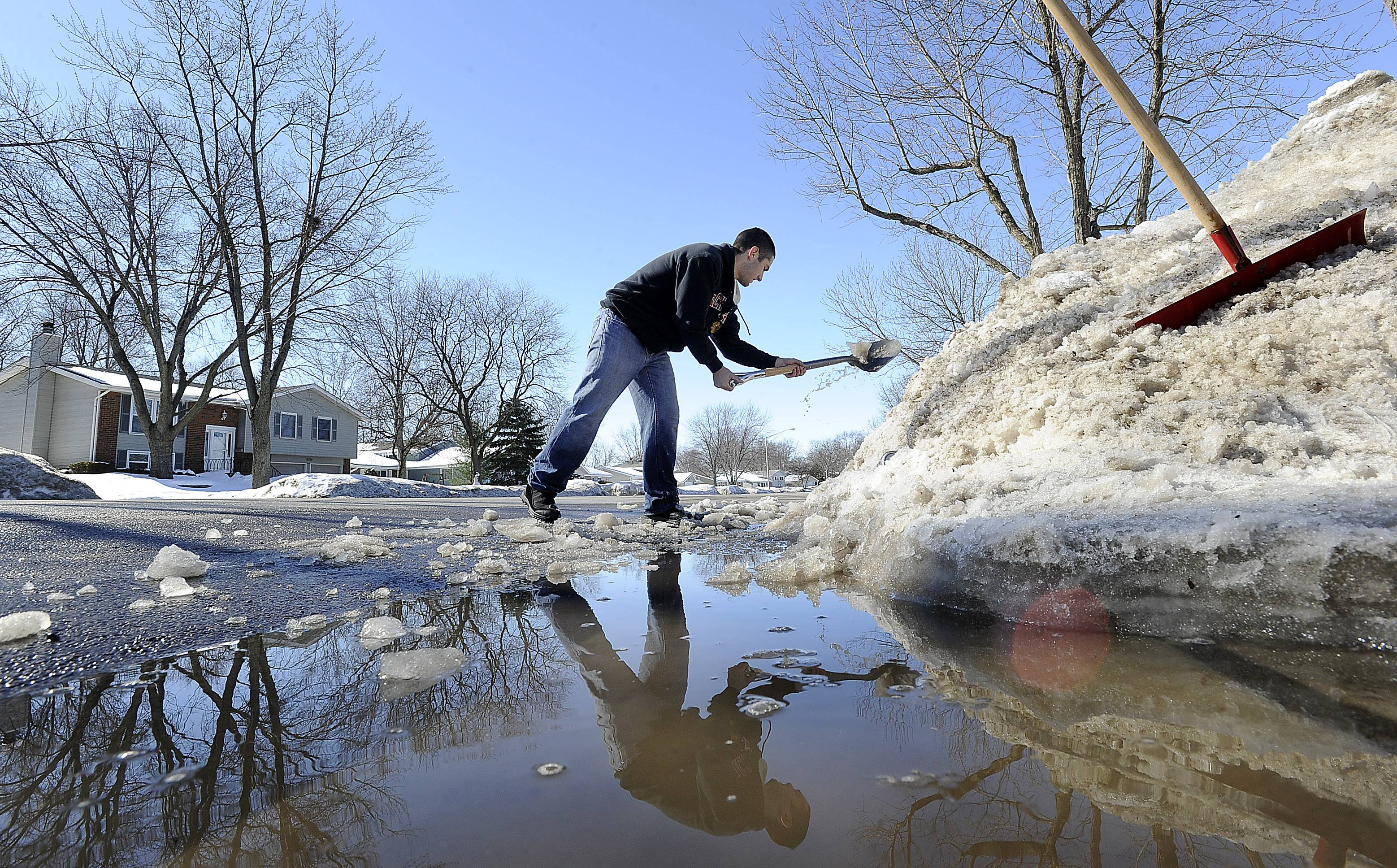 "Mike Hamlin, 26, of Schaumburg, clears out the ice and snow from his driveway as his house sits on a low end of the road as the winter thaw starts. ""It was a couple of inches deep, enough to cover my foot,"" he said as his first order of business was to clear the grate in the street. For over two hours until it was time for him to leave for work he chopped away at ice chunks at the end of his driveway and street."