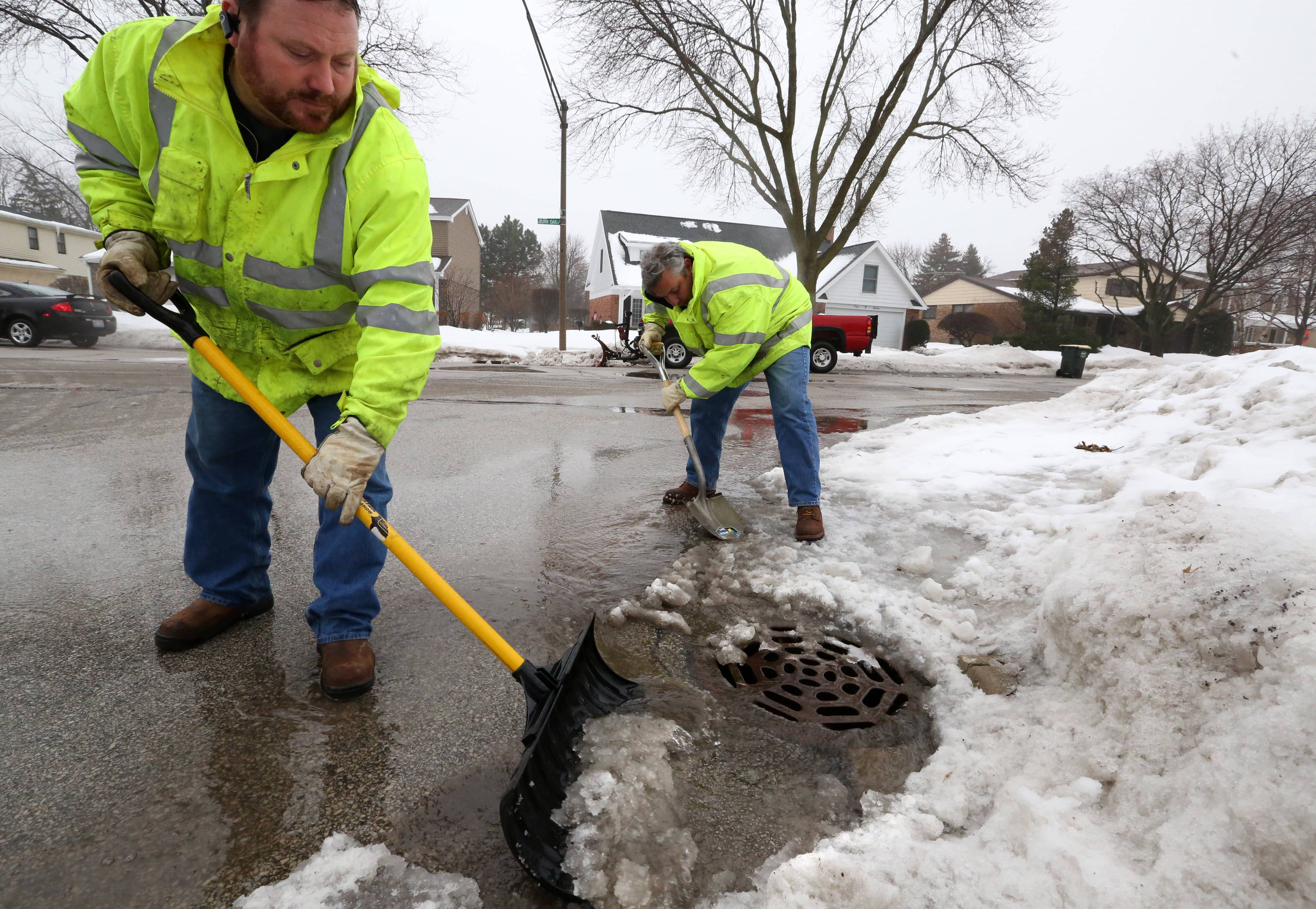 Arlington Heights sewer and streets workers Jim Schmid and Shawn McAlpin clear a street drain in the Northgate subdivision on Thursday in Arlington Heights.