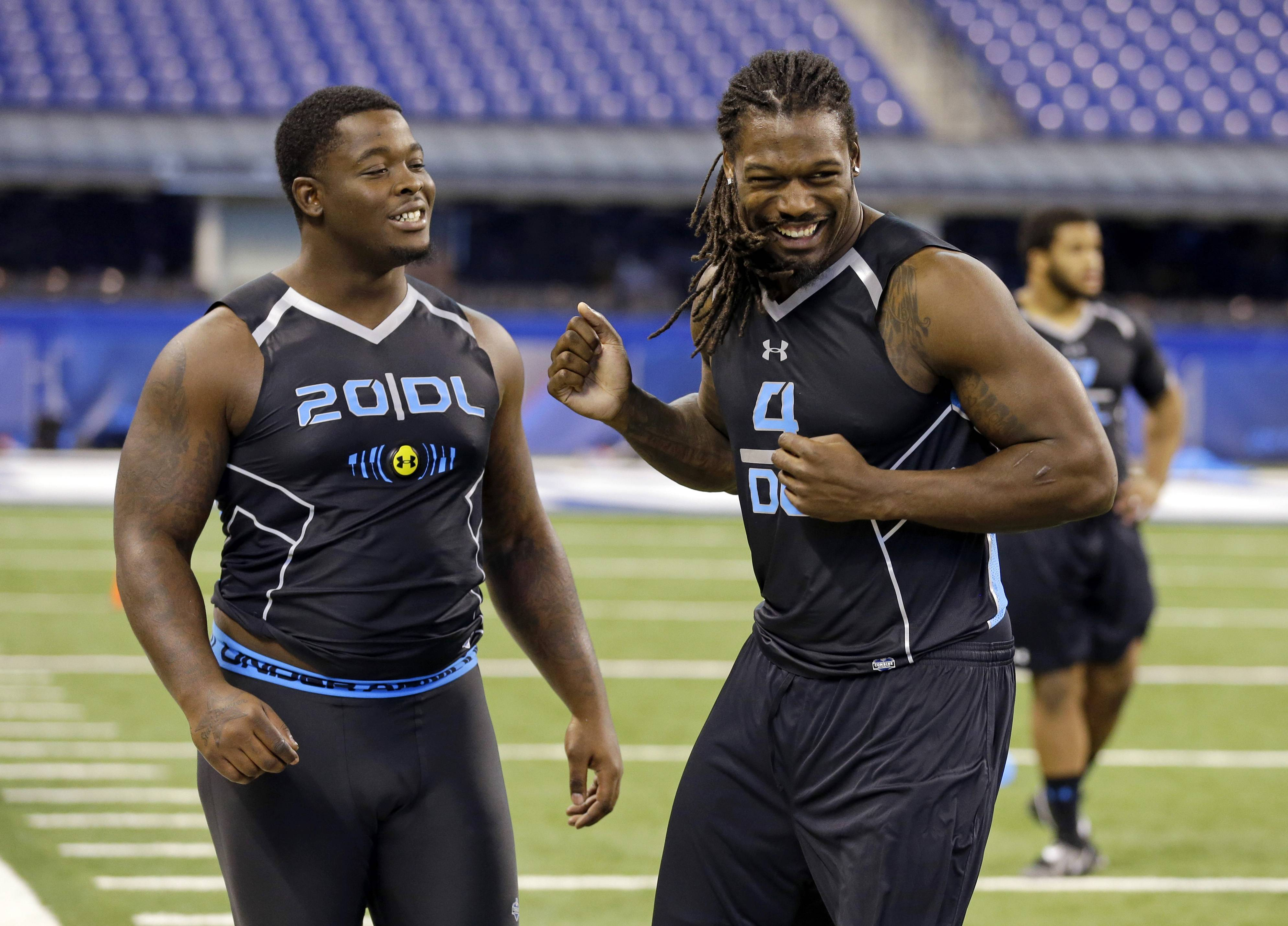 South Carolina defensive lineman Jadeveon Clowney, left, jokes with Florida State defensive lineman Timmy Jernigan during drills at the NFL football scouting combine Monday in Indianapolis.