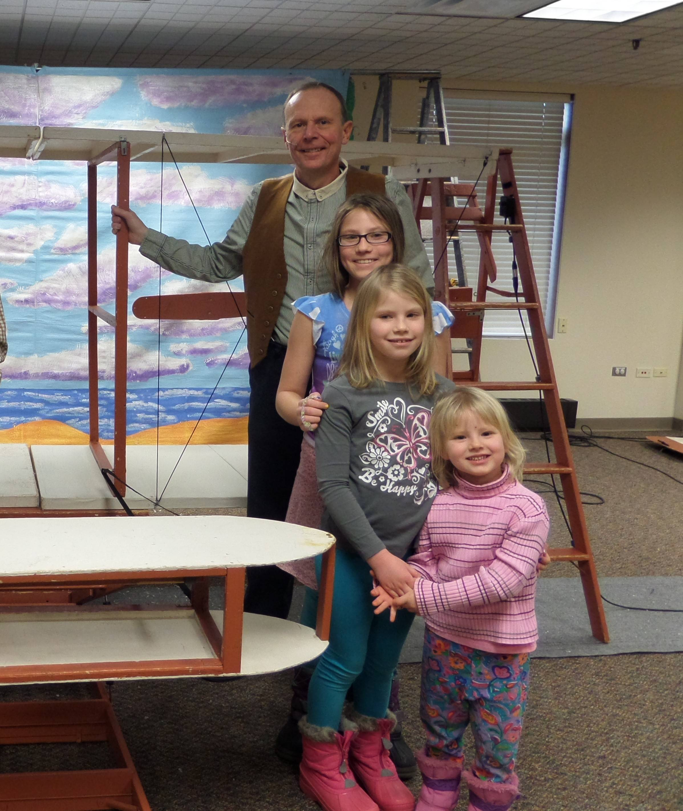 The King sisters share a moment with Wilbur Wright and the historical flyer at the Barltett Public Library. Pictured, from left, are Face to Face Production's Mark Grimsich and Bartlett residents Aria, Rylee and Clarice King.