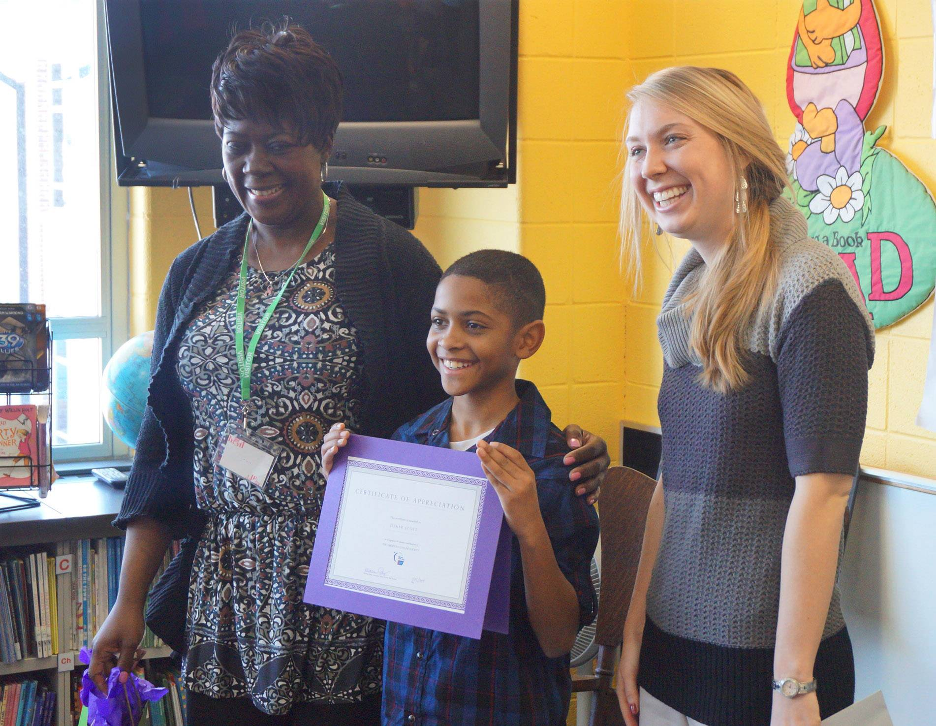 Woodland Elementary East student Demar Scott, center, presented a check to Kristina Eddy, right, of the American Cancer Society in honor of his grandmother, Doris Moore, left, of Gurnee. Moore was recently diagnosed with breast cancer.