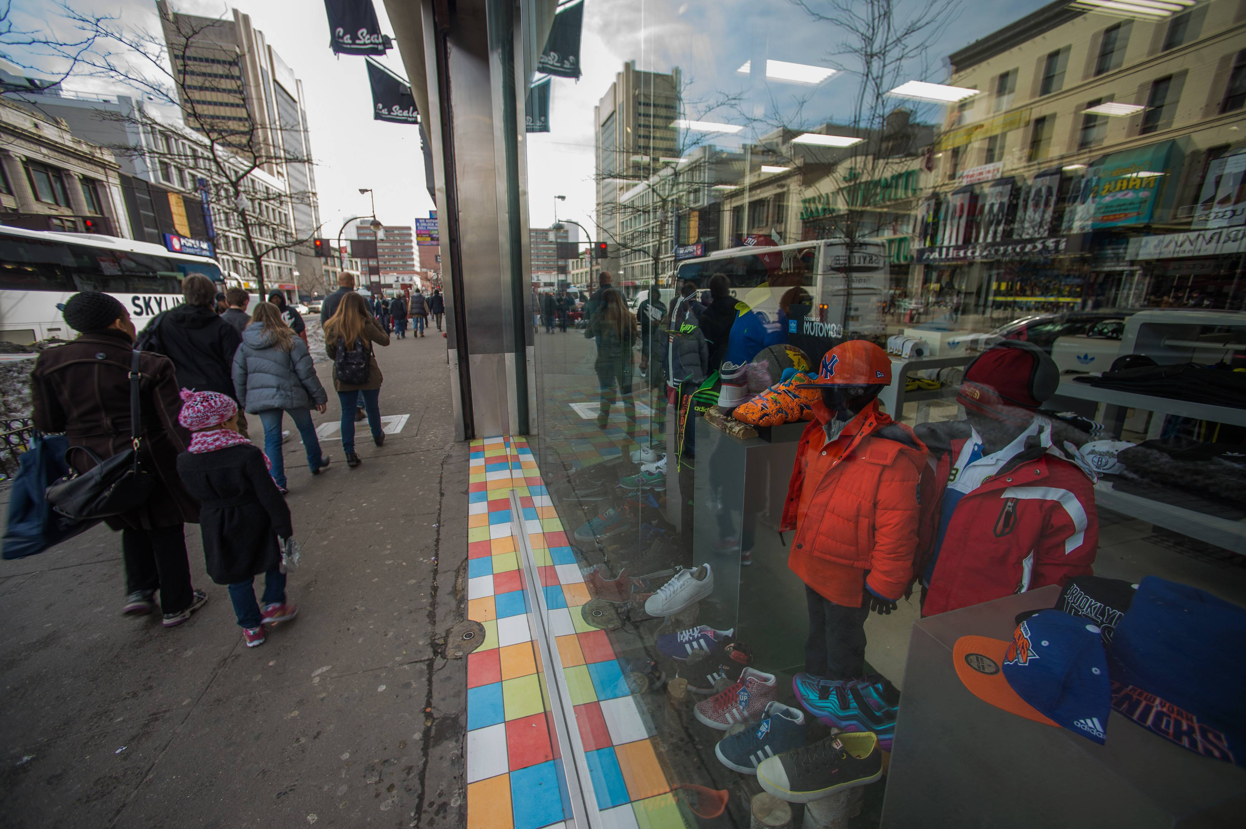 Pedestrians walk past the display window of a store in the Harlem neighborhood of New York, U.S. Consumer confidence in the U.S. fell more than forecast in February as Americans grew more pessimistic about the outlook for the economy and employment.
