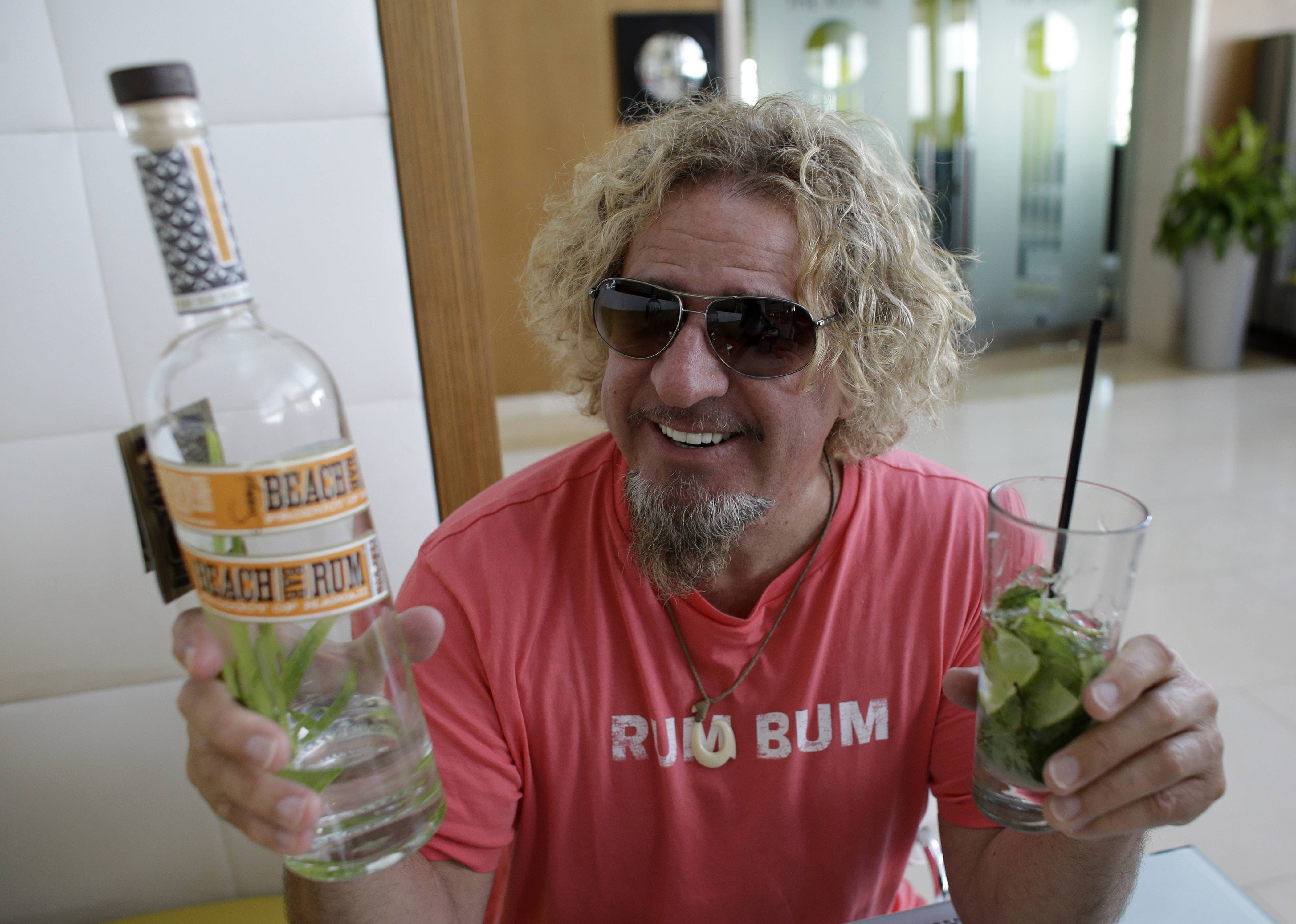 Musician Sammy Hagar holds a bottle of his Beach Bar Rum, and a mojito made with the rum, during a recent interview in Miami.