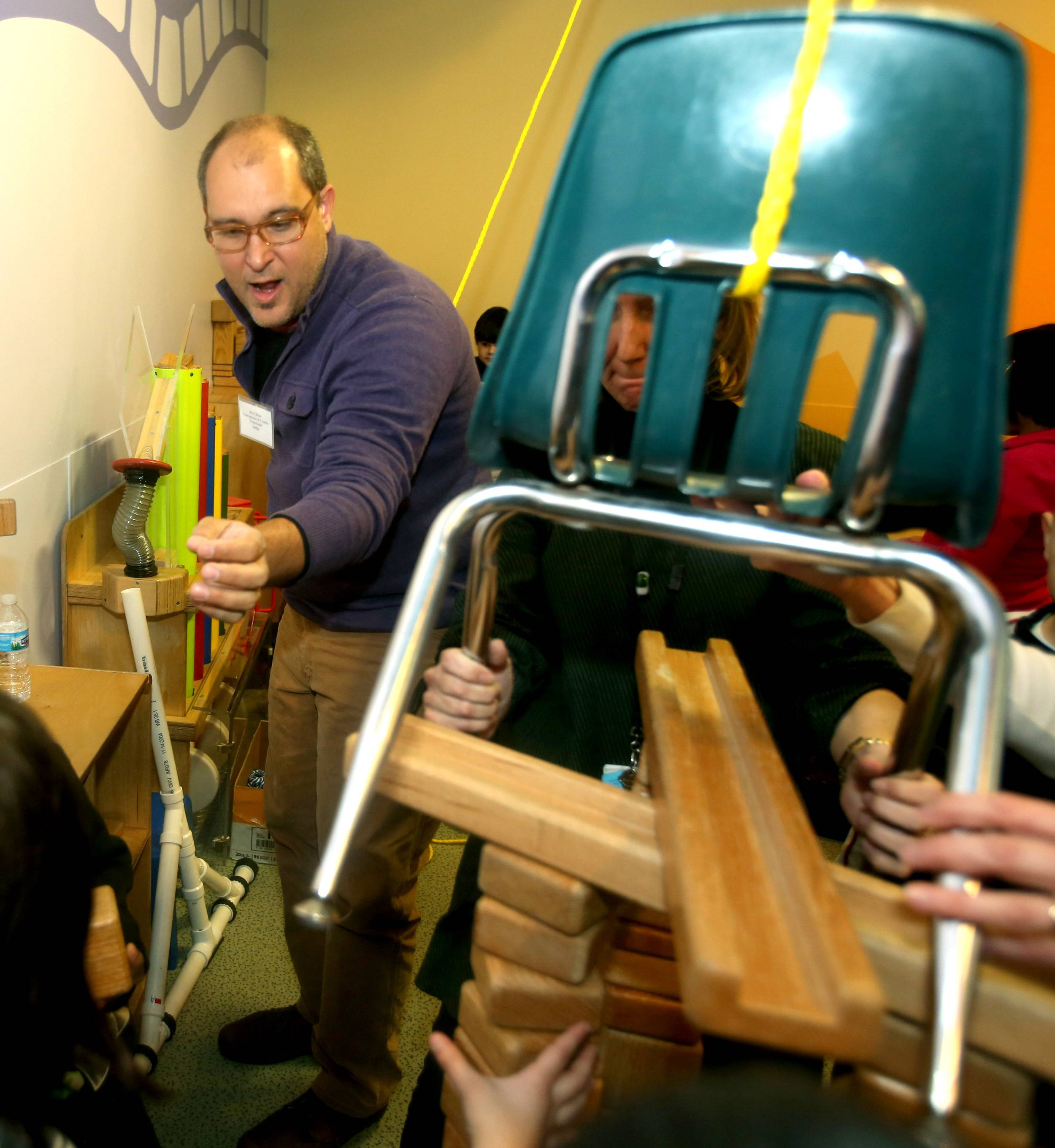 "Creative technologist Brett Doar, known as Hollywood's ""King of Creative Contraptions,"" works with students from John W. Gates Elementary in Aurora to build a Rube Goldberg-inspired machine Tuesday at the DuPage Children's Museum in Naperville."