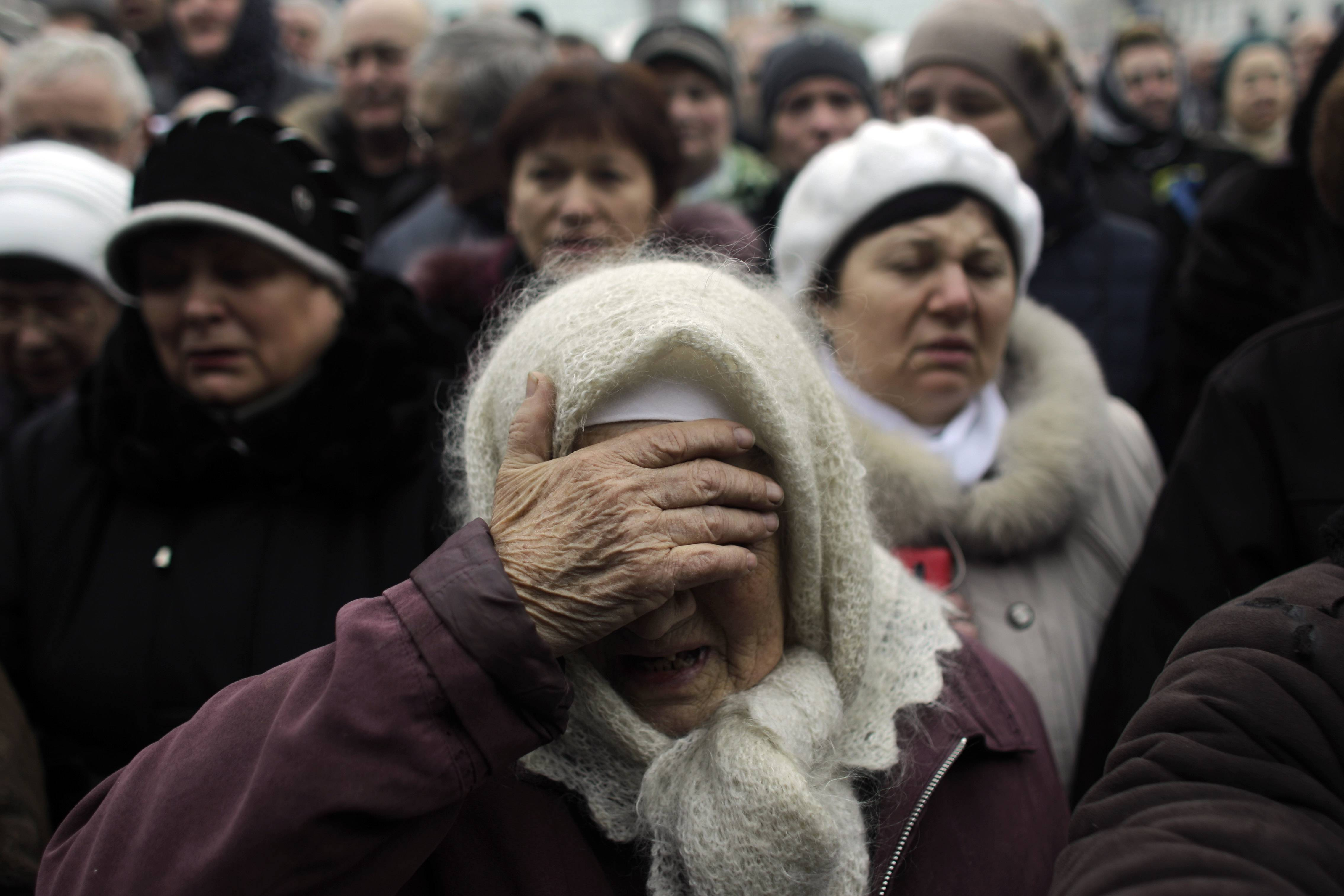 A woman reacts at a memorial for the people killed in clashes with the police at Kiev's Independence Square, the epicenter of the country's current unrest, Ukraine, Tuesday. The Ukrainian parliament on Tuesday delayed the formation of a new government, reflecting political tensions and economic challenges following the ouster of the Russia-backed president.