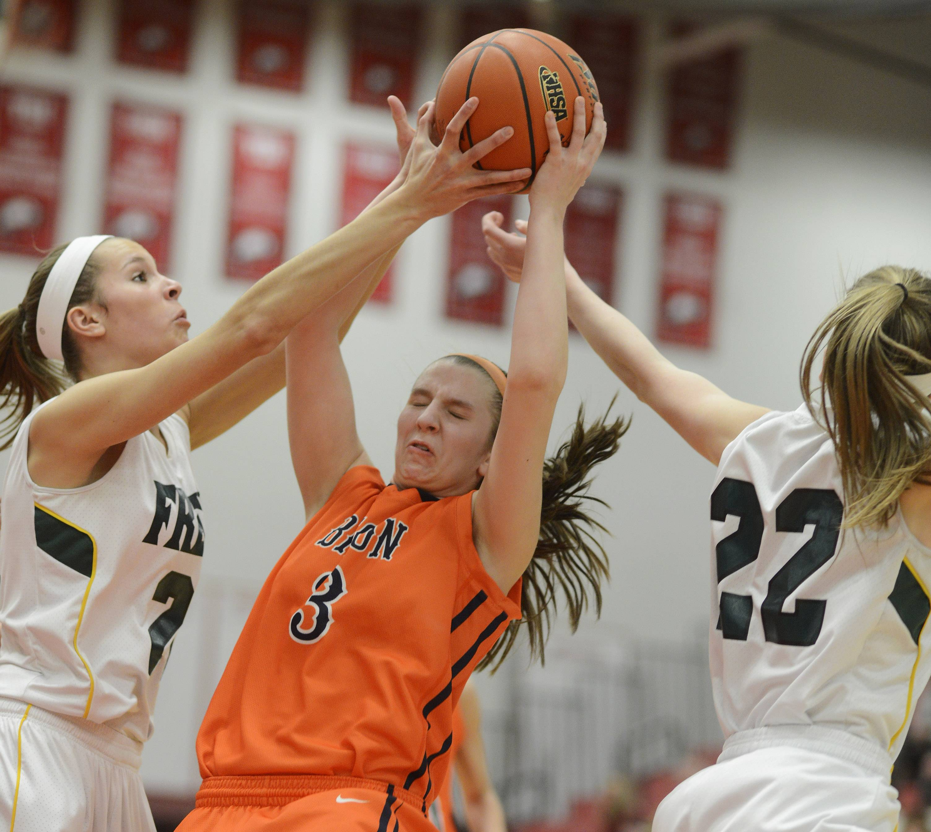 Buffalo Grove's Maddie Welter, middle, gets between Fremd's Grace Twrek, left, and Erin Lenahan for a rebound.