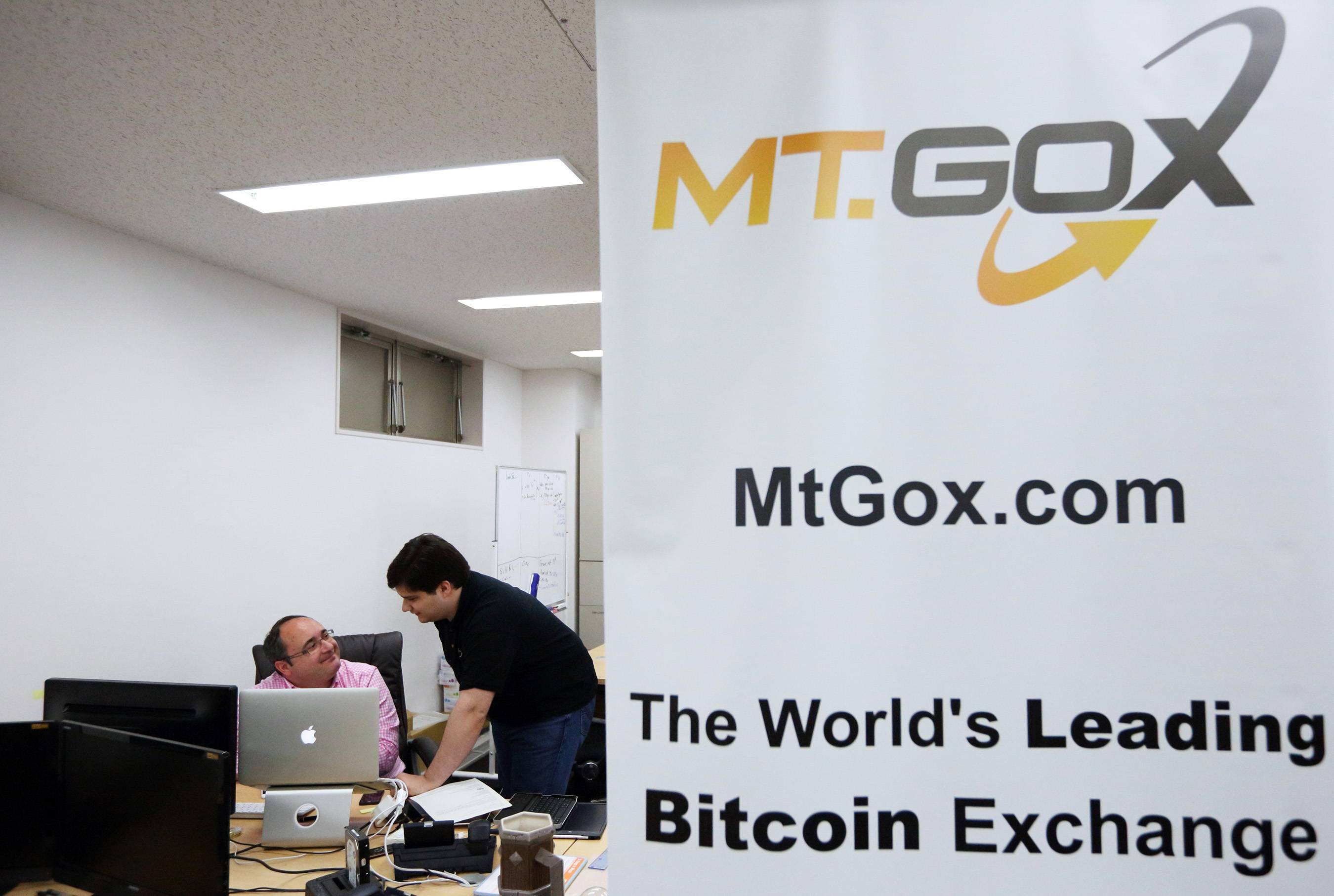Mark Karpeles, chief executive officer of Tibanne Co., right, speaks to an employee in the office operating the Mt.Gox K.K. bitcoin exchange in Tokyo, Japan, in April 2013. Bitcoin digital currency, which carries the unofficial ticker symbol of BTC, was unveiled in 2009 by an unidentified programmer, or group of programmers, under the name of Satoshi Nakamoto. Supply is capped