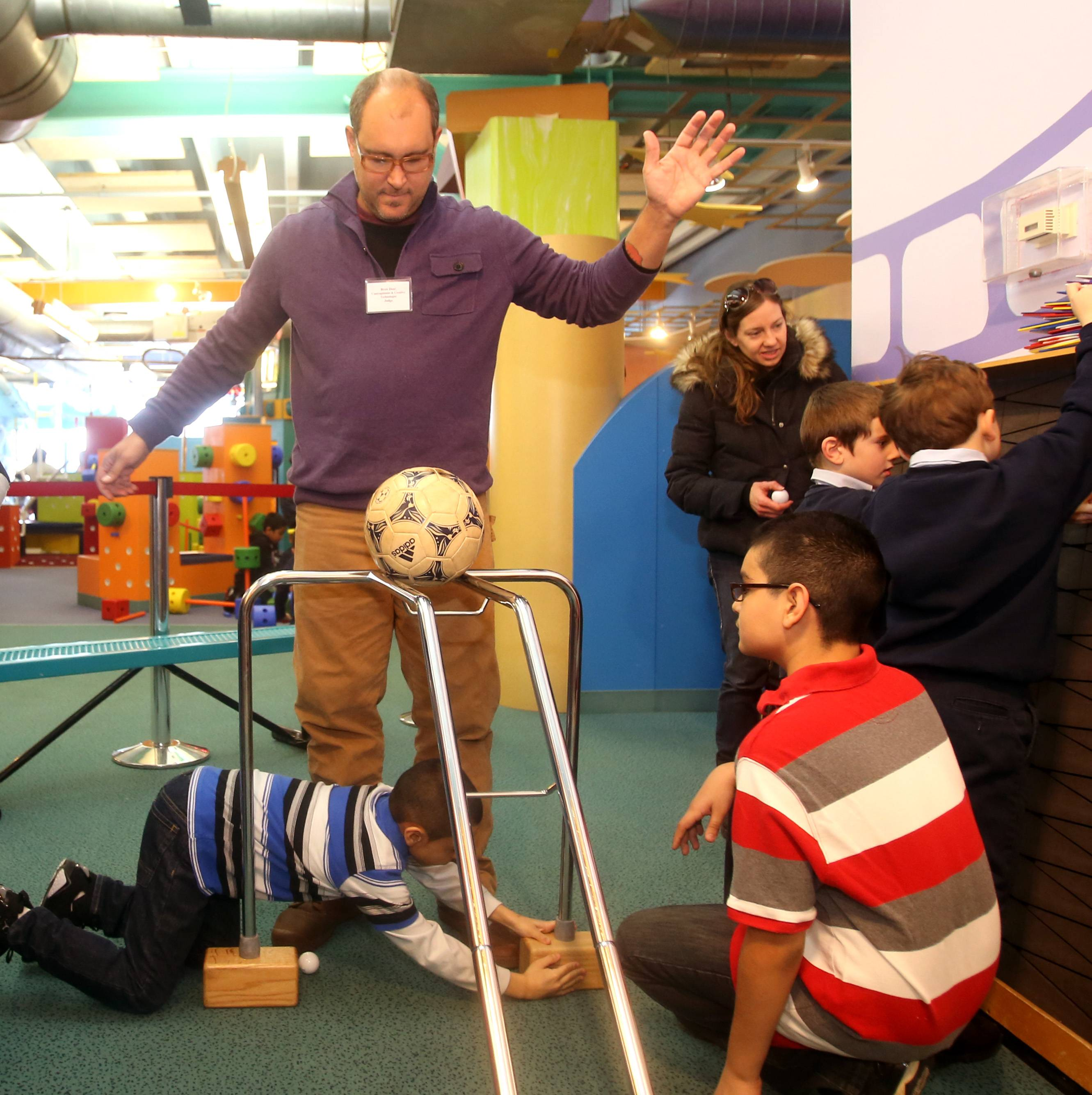 "Brett Doar, known as Hollywood's ""King of Creative Contraptions"" tests part of a Rube Goldberg-inspired machine as he helps students build it Tuesday morning at DuPage Children's Museum in Naperville. Students from John W. Gates Elementary in Aurora built the machine in advance of an Innovation Open House the museum held Tuesday evening."