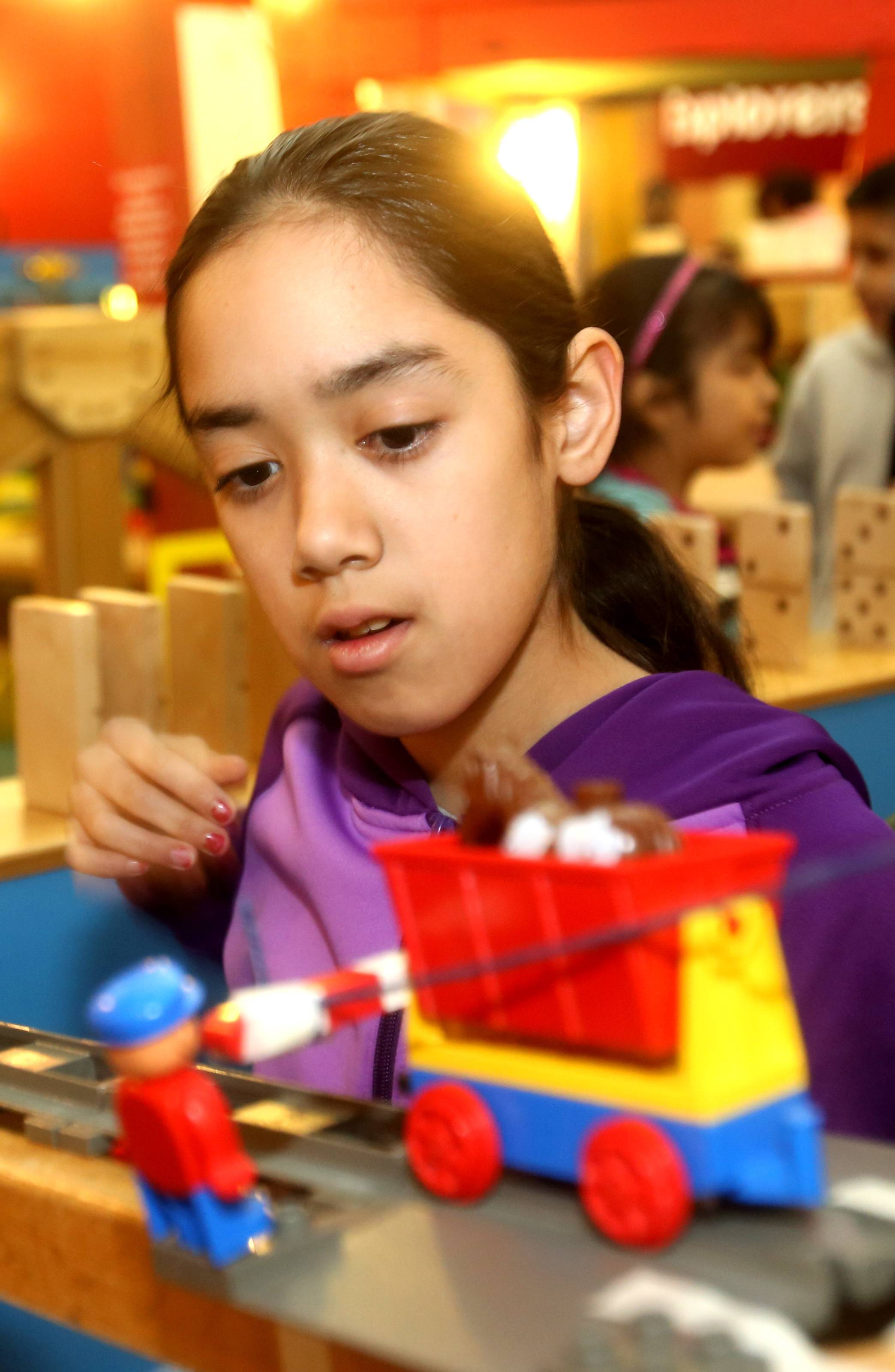 "Elizabeth Galindo, 11, of Aurora, works under the guidance of Hollywood's ""King of Creative Contraptions"" Brett Doar on Tuesday as she helps build a Rube Goldberg-inspired machine at DuPage Children's Museum in Naperville."