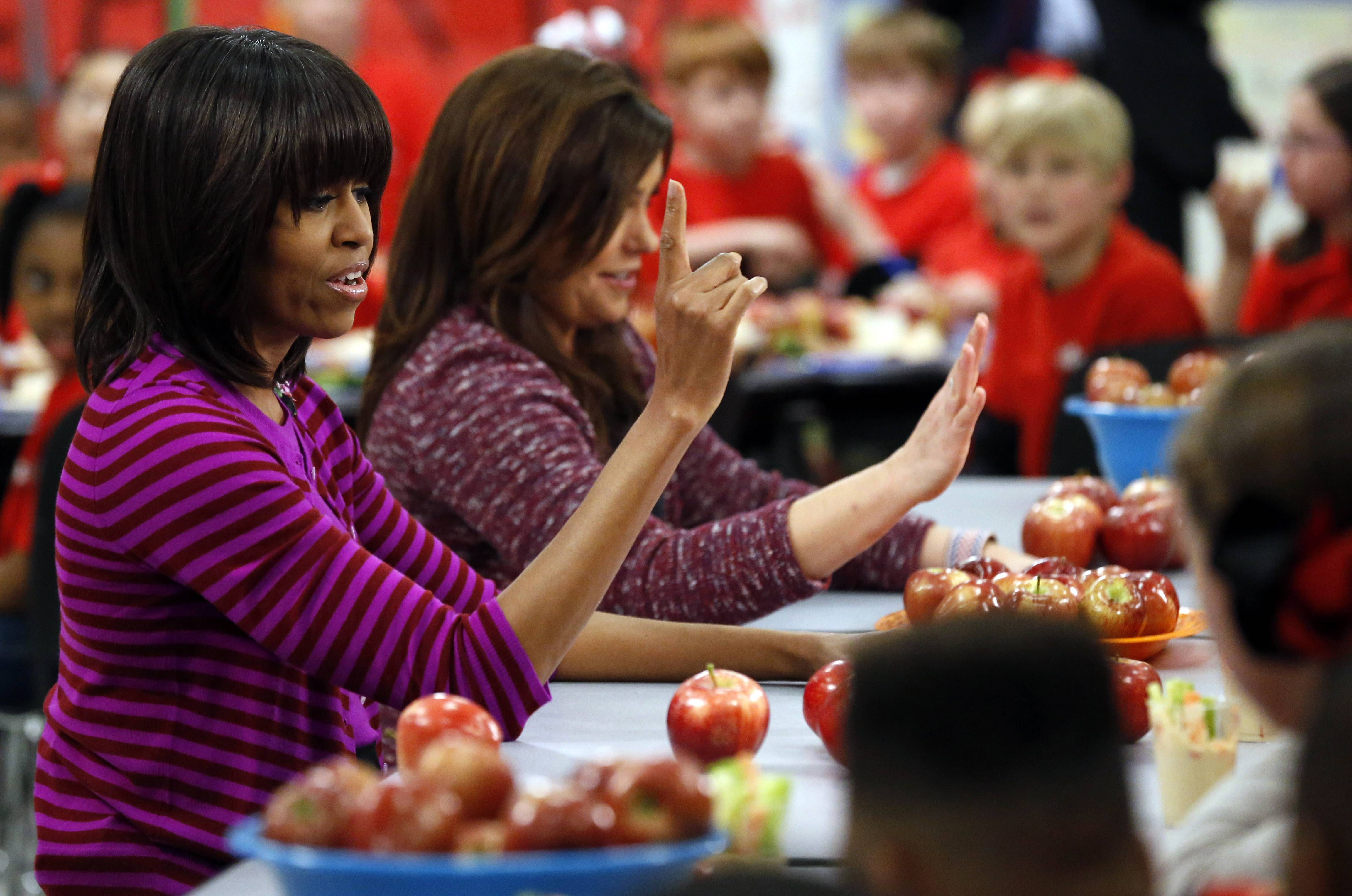 First lady Michelle Obama and Food Network chef Rachel Ray discussing lunches with students in Clinton, Miss. Moving beyond the lunch line, new rules expected to be proposed by the White House and the Agriculture Department Tuesday, Feb. 25, 2014, would limit marketing of unhealthy foods in schools.