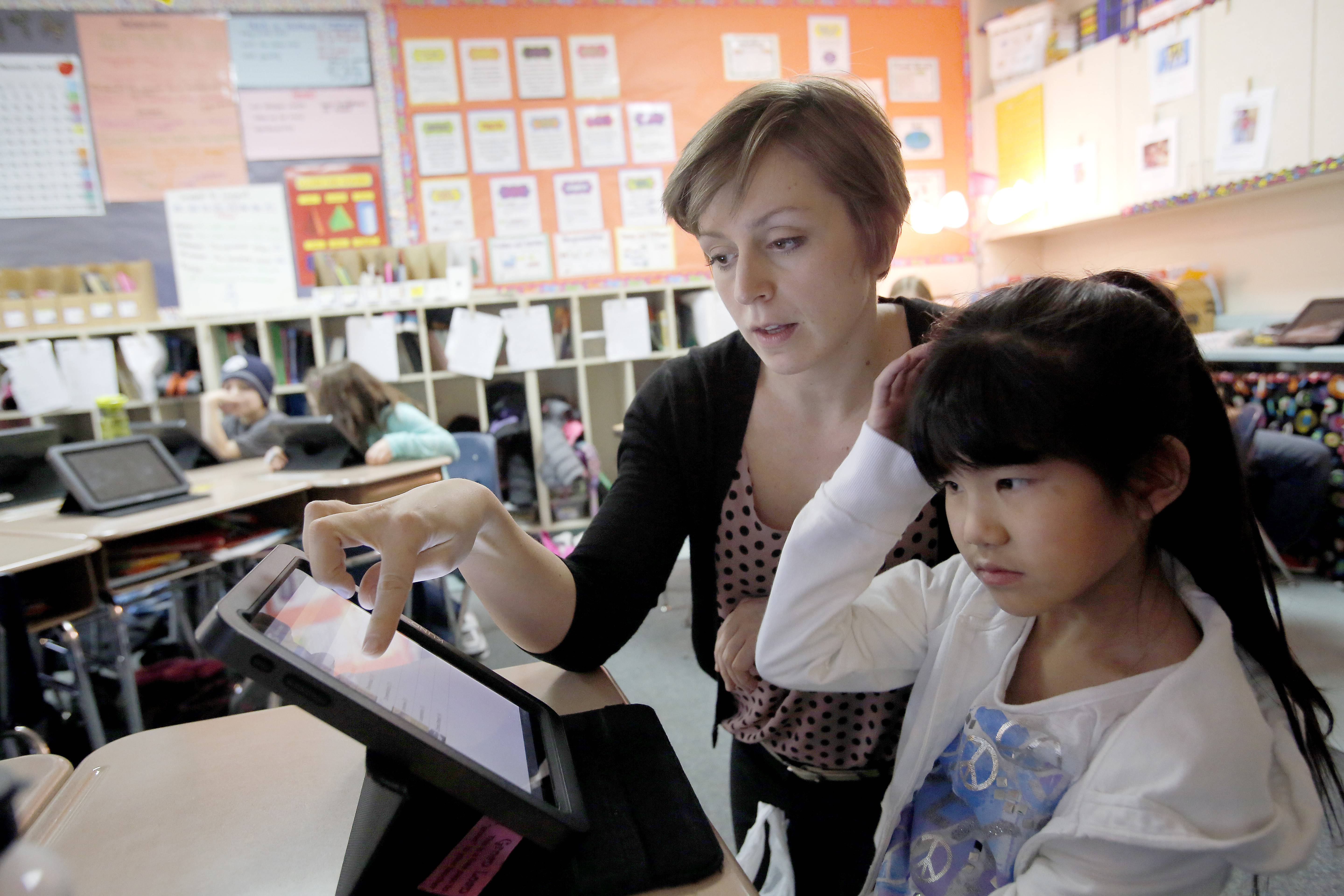 "Marisa Burkhart, director of educational technology for Huntley School District 158, works with third-grader Alexa Brown, 9, on her tablet. Burkhart has been named the Illinois Computing Educators ""Educator of the Year."""