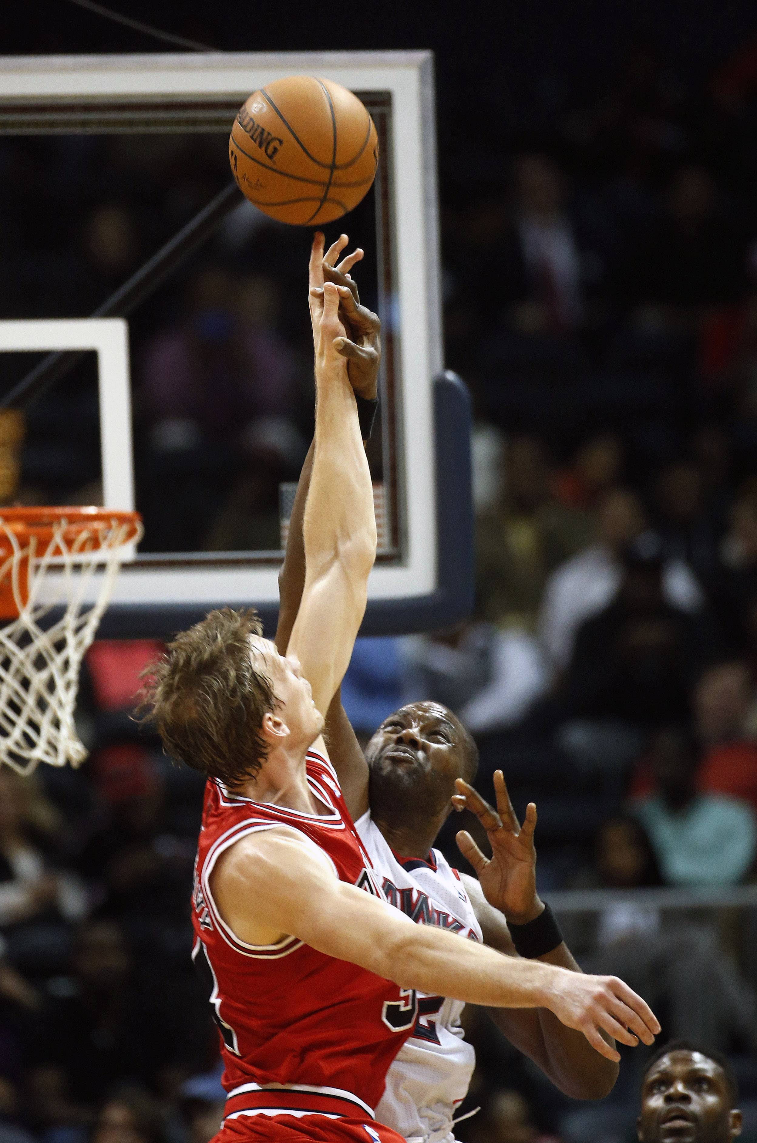 Atlanta Hawks power forward Elton Brand (42) and Chicago Bulls small forward Mike Dunleavy (34) battle for control on a jump ball in the first half of an NBA basketball game  Tuesday, Feb. 25, 2014, in Atlanta.