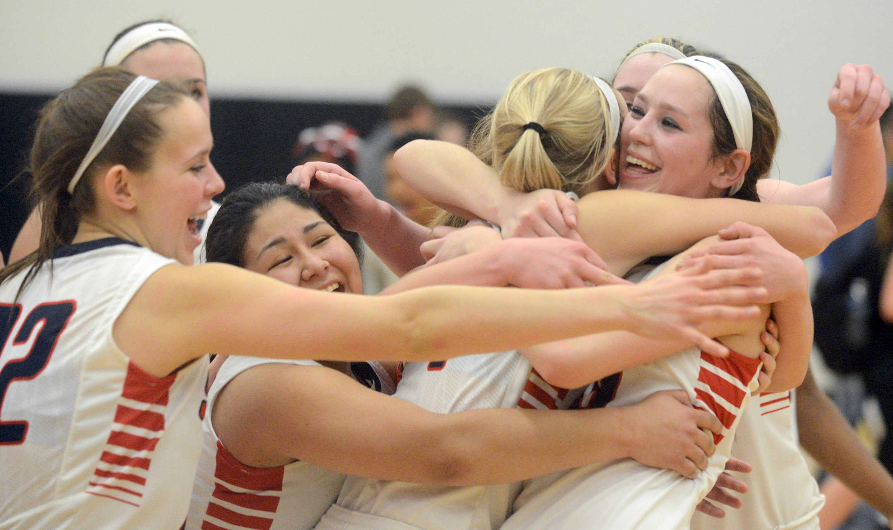 South Elgin's Laura McIntosh, left, Nadia Yang, center, and Kennede Miller share a group hug after Thursday's Class 4A Jacobs regional championship girls basketball game in Algonquin.