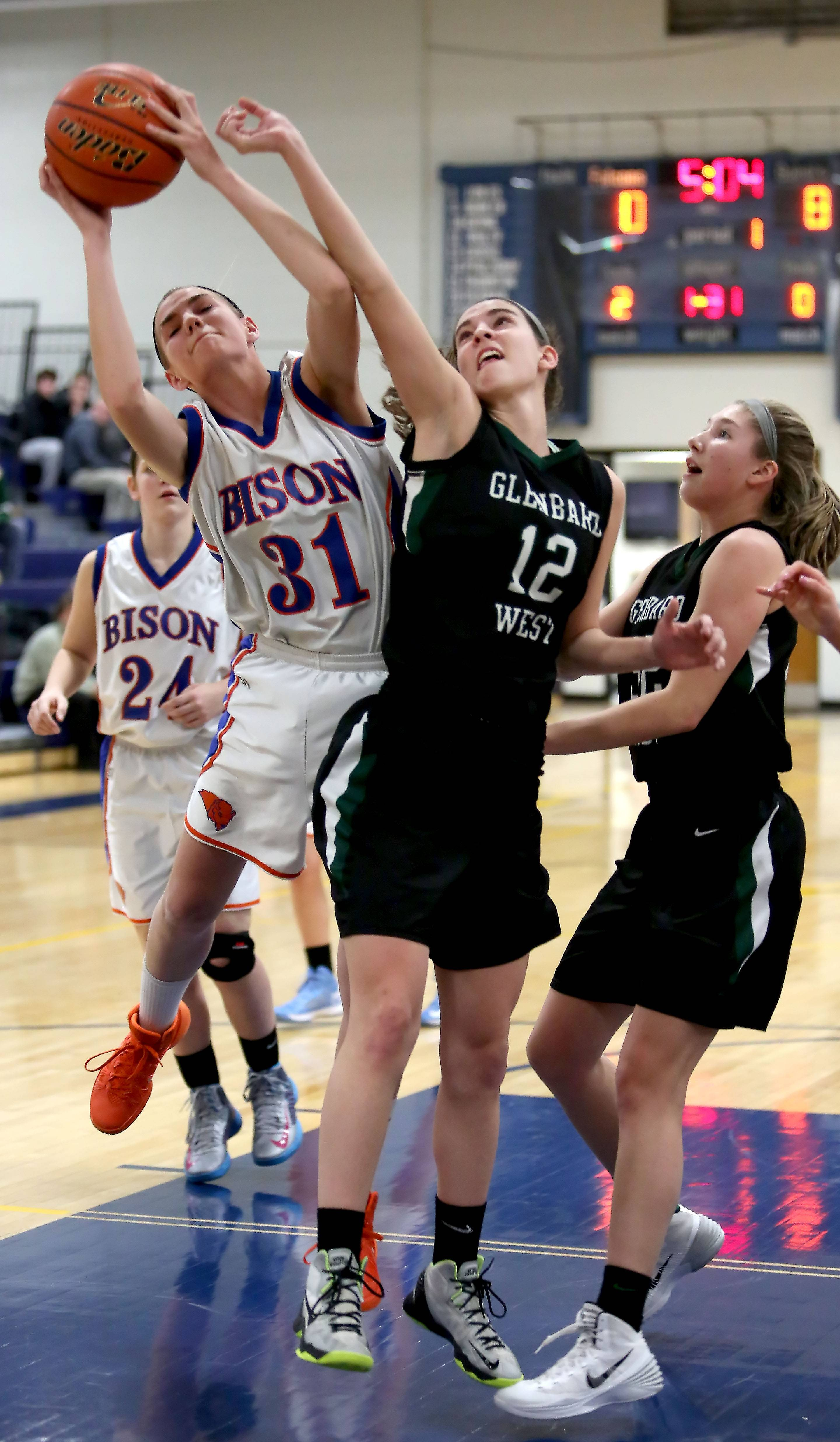 Fenton's Dana Fritz, left, and Glenbard West's Marisa Vivodago reach for a rebound in Monday's regional basketball game at Wheaton North.