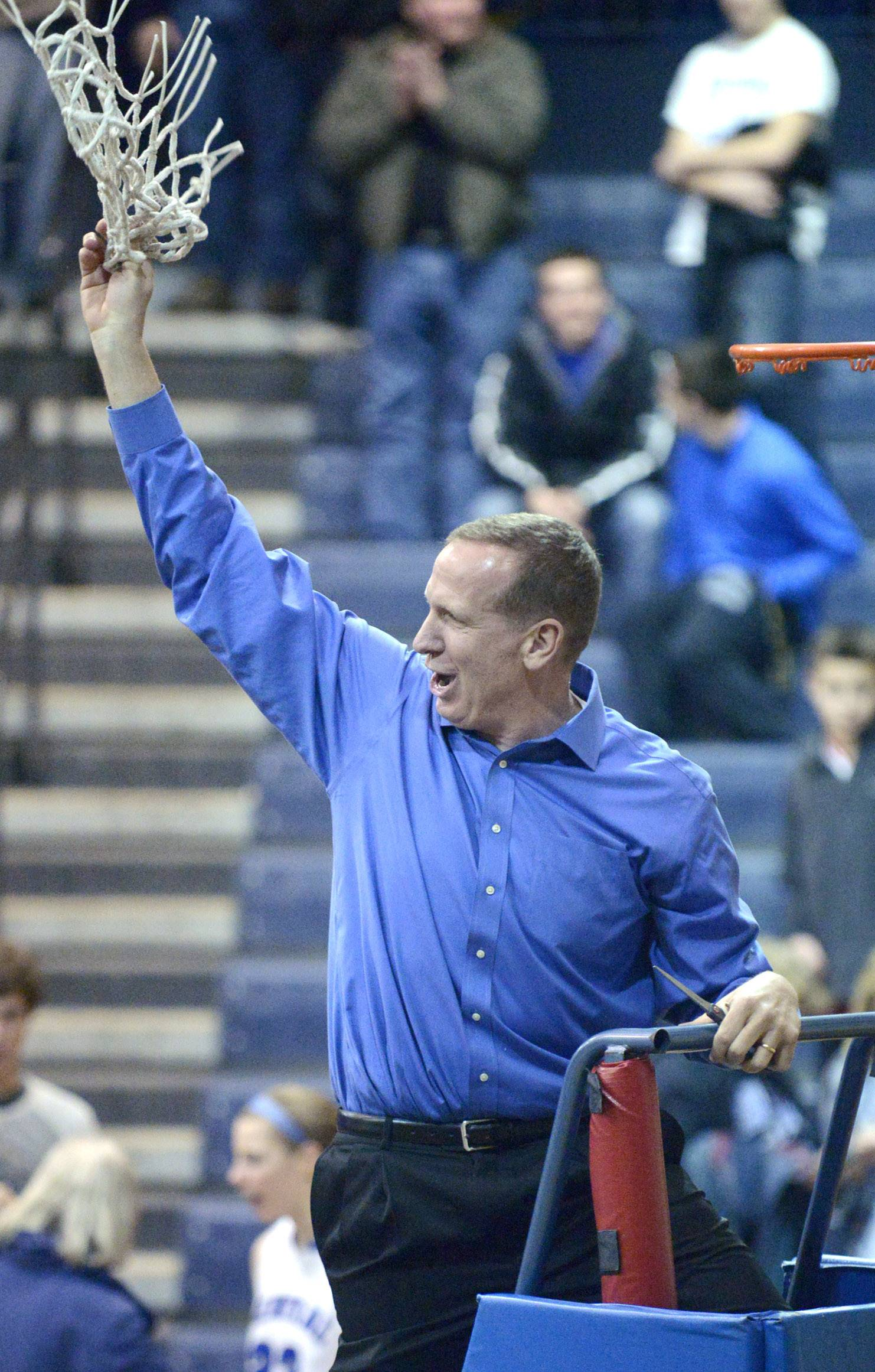 Burlington Central head coach Mark Smith twirls the hoop in the air after defeating St. Edward in Saturday's  Class 3A regional championship.