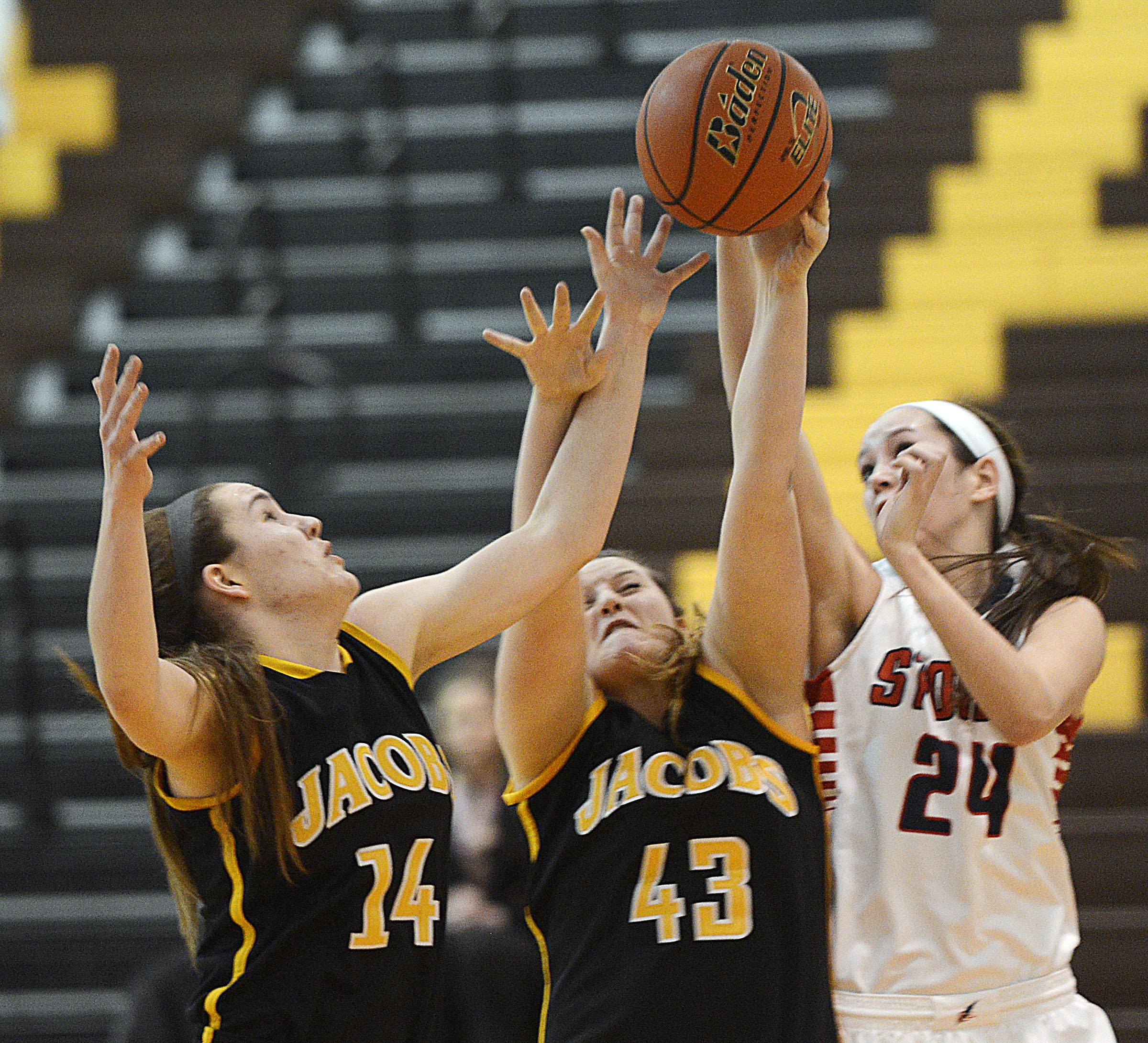 Jacobs and South Elgin players reach for a rebound Tuesday in Algonquin.