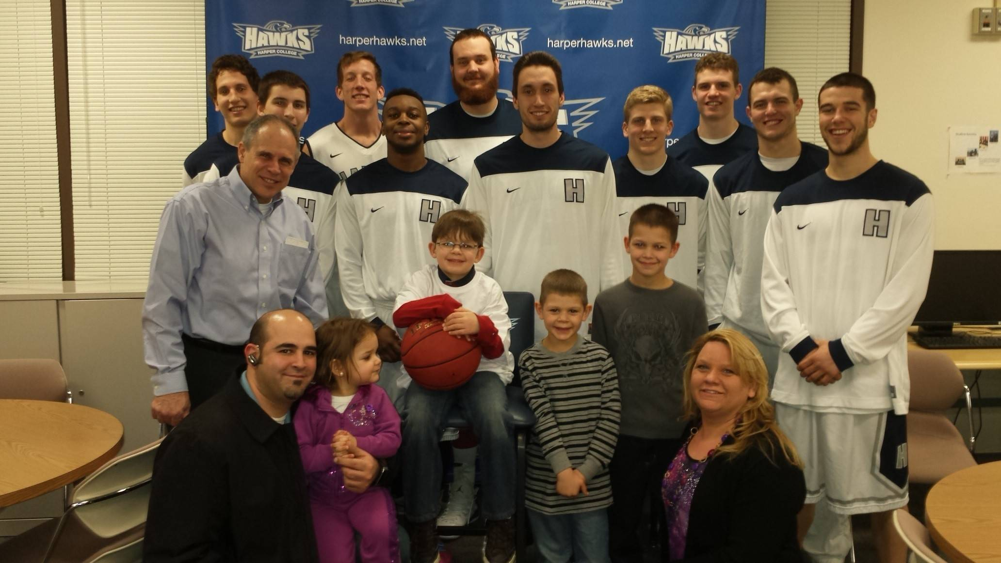 Kadeen Alansari, center with basketball, along with his family and the Harper College men's basketball team prior to the final home game.