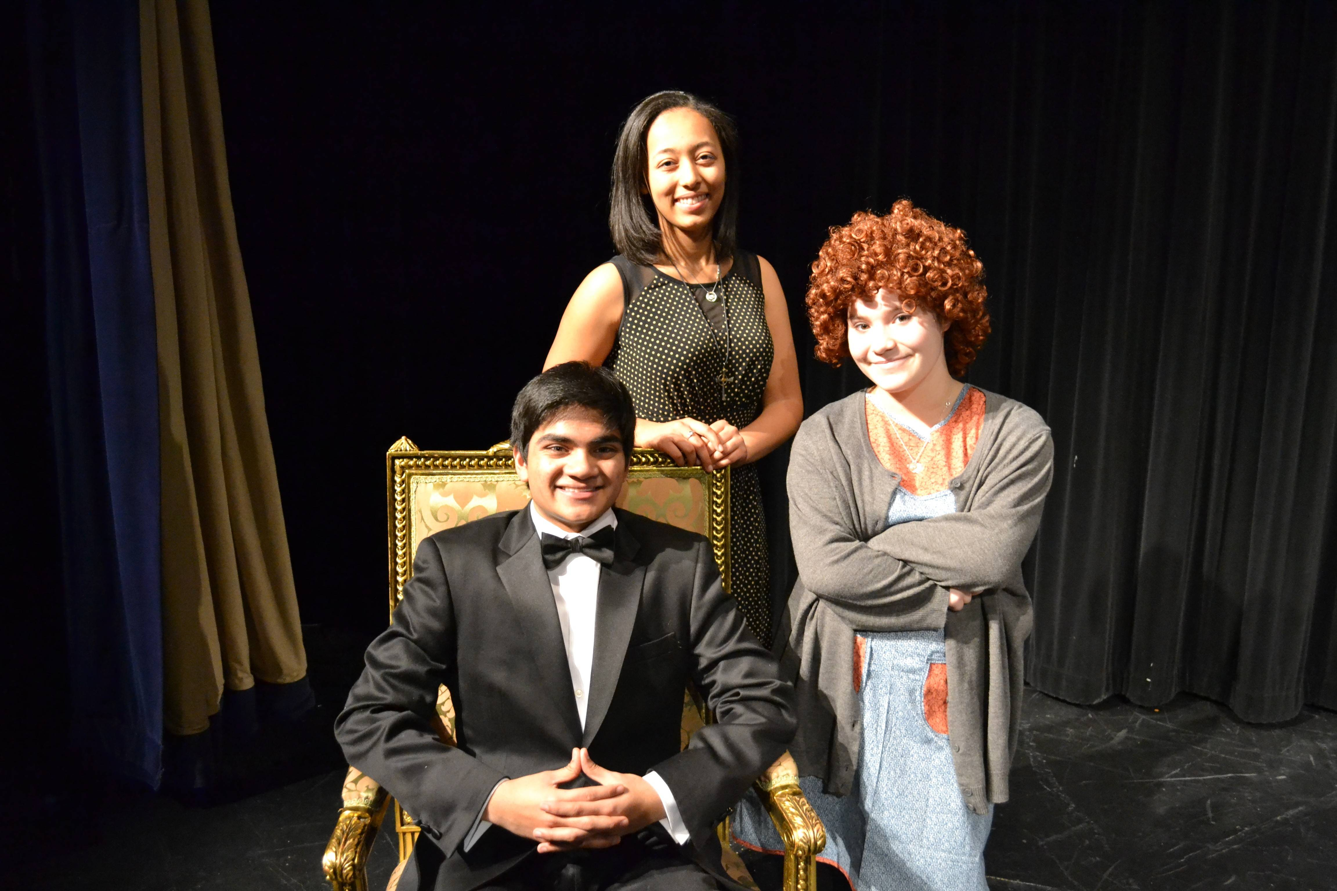 "Ian Joseph as Oliver Warbucks, Kendra Alexander as Grace Ferrell; and Rebecca Fuscone as Annie in the Hoffman Estates High School production of ""Annie."" Costumes courtesy of Mrs. Ecker and the Hoffman Estates High School Fashion class."