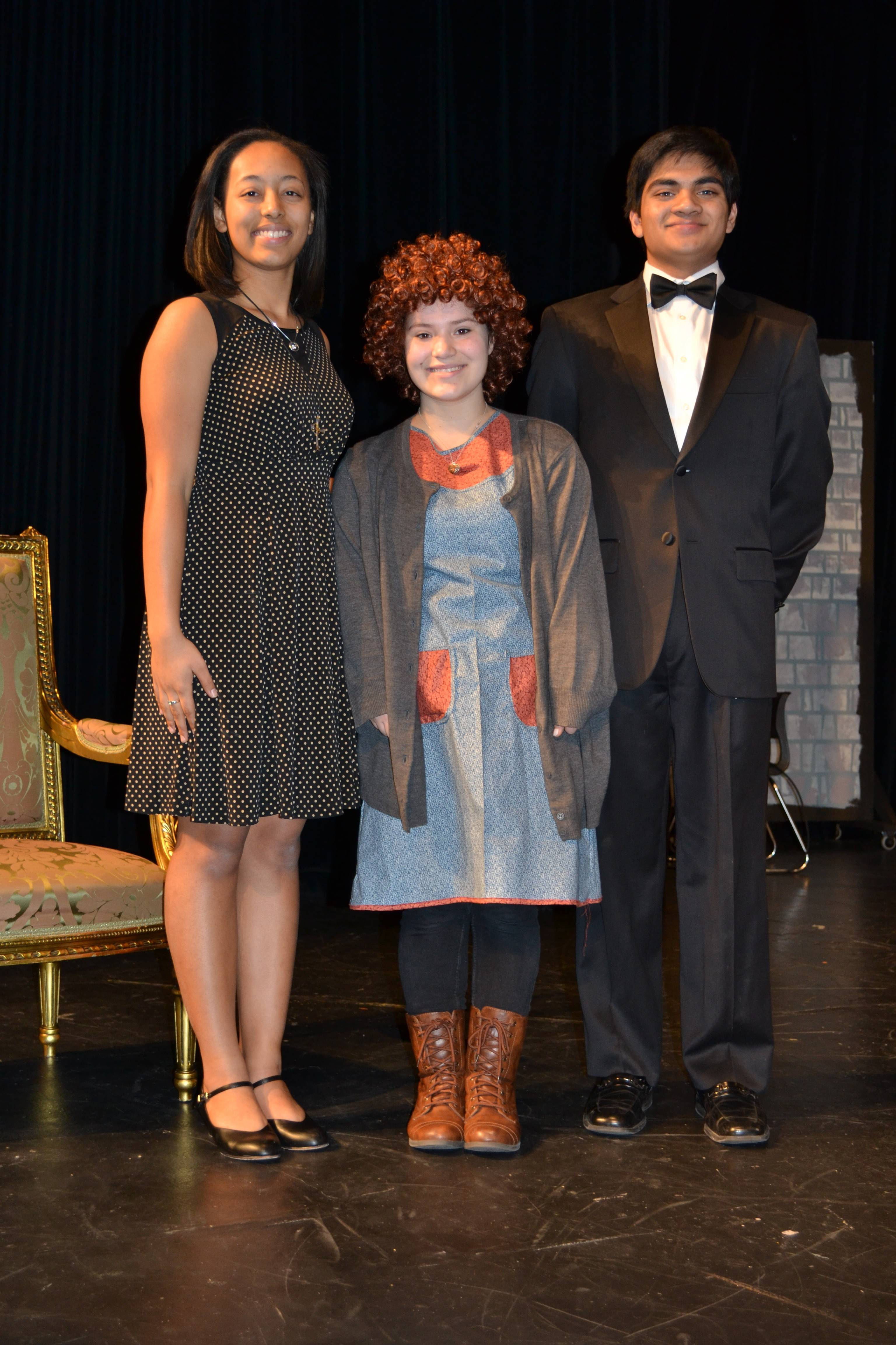 "Kendra Alexander as Grace Ferrell; Rebecca Fuscone as Annie; and Ian Joseph as Oliver Warbucks, in the Hoffman Estates High School production of ""Annie."" Costumes courtesy of Mrs. Ecker and the Hoffman Estates High School Fashion class."