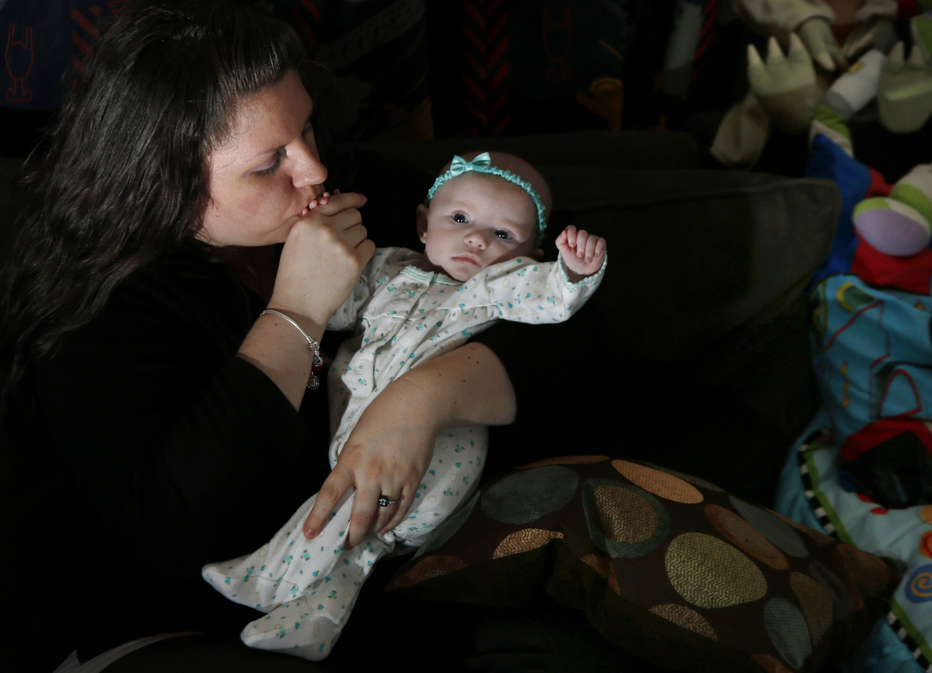 Jennifer Fontaine kisses her baby daughter, Morgan. After Fontaine's standard prenatal screening suggested her fetus might have Edwards syndrome, a doctor suggested a fetal DNA test, which suggested her fetus was fine.