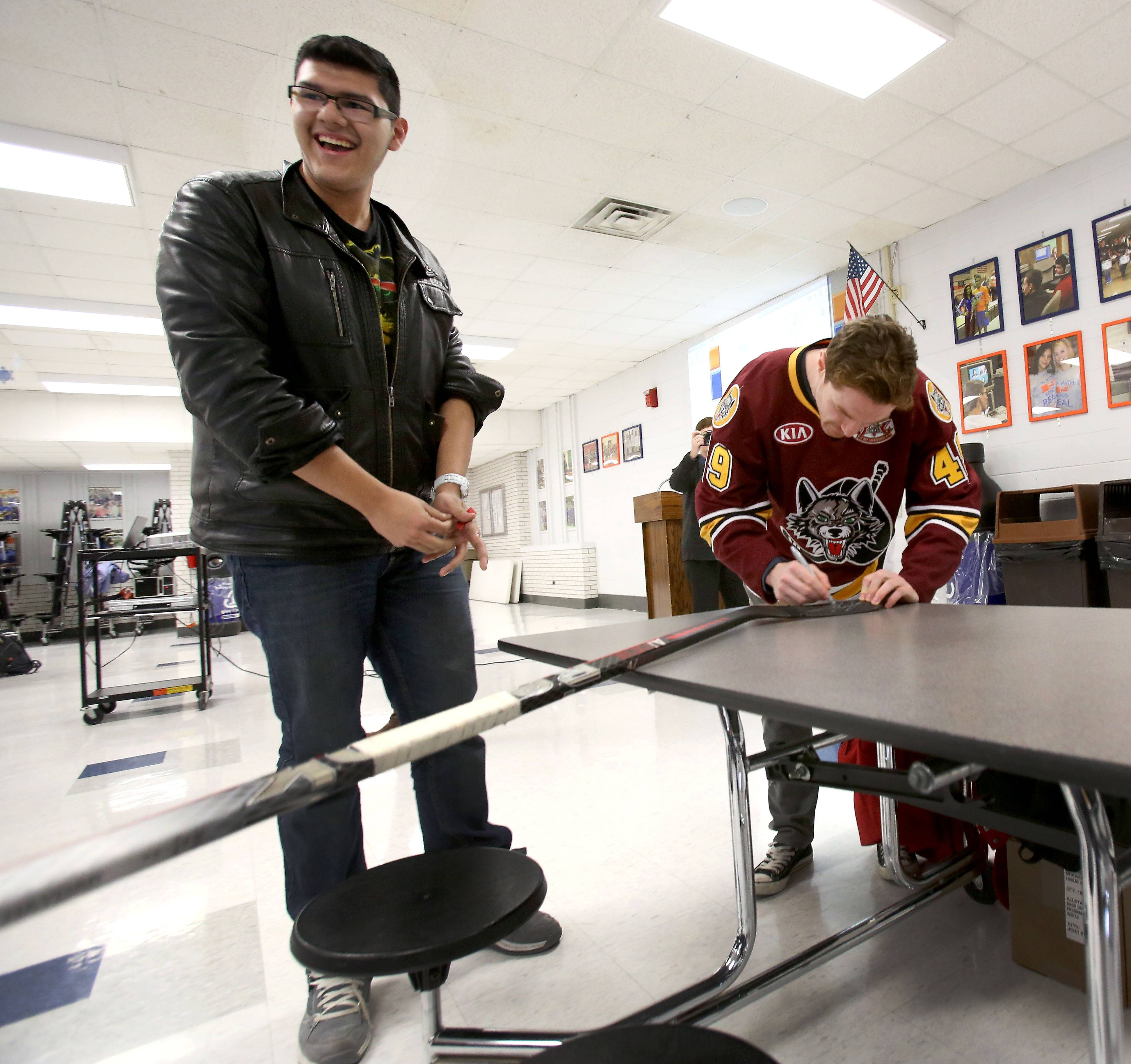 Fenton High School junior Pedro Huerta is all smiles Wednesday as Chicago Wolves center Alexandre Bolduc signs a hockey stick for him. Pedro won it in a raffle as Bolduc met with students studying French at the Bensenville school.