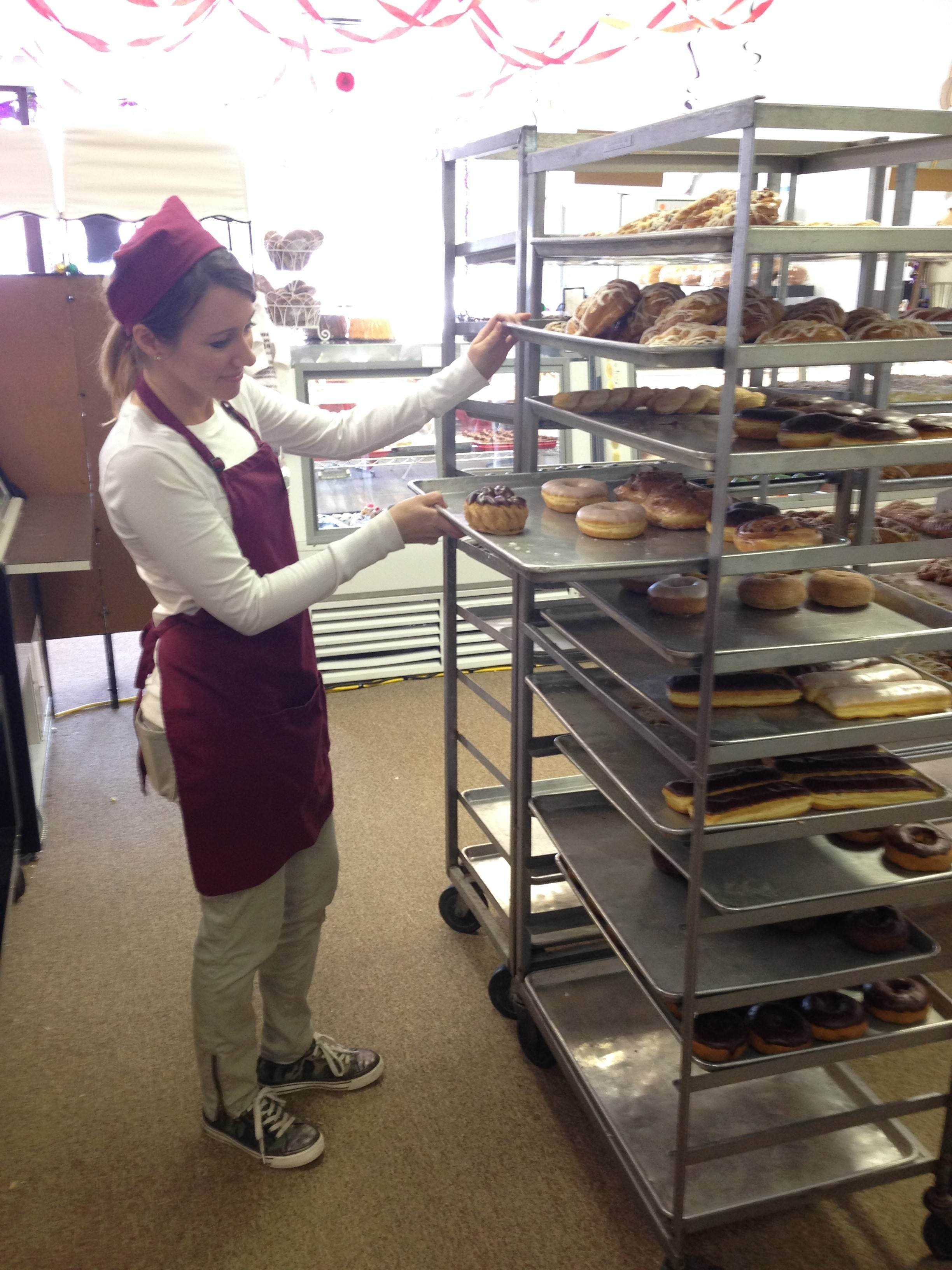 Katie Collins checks a tray of doughnuts Wednesday inside Central Continental Bakery's temporary location at 17 W. Prospect Ave. in downtown Mount Prospect. The bakery was displaced from its longtime location on Main Street in Mount Prospect by a Feb. 9 fire.