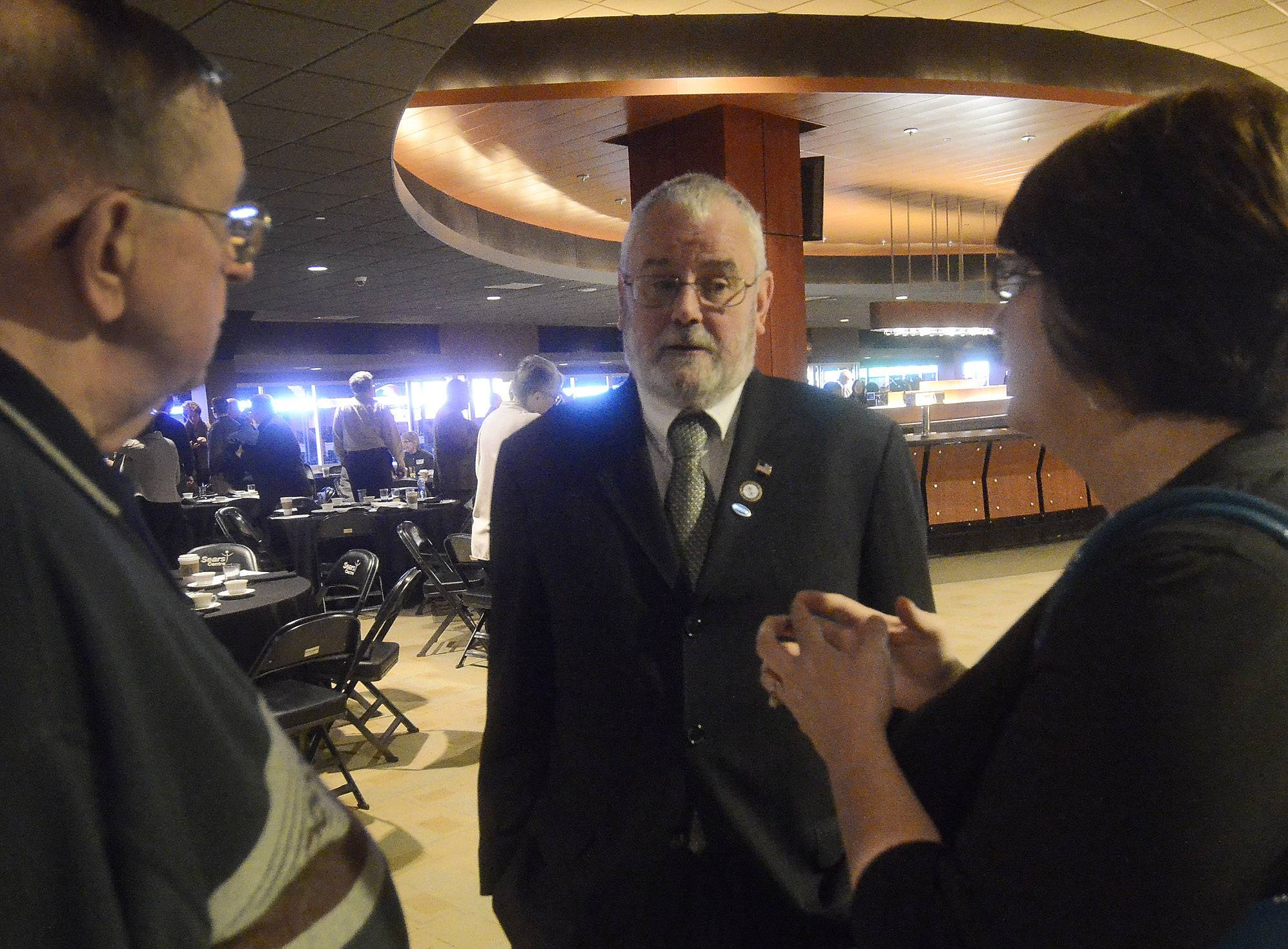 Hoffman Estates Mayor Bill McLeod talks with Steve Wilson and Tonya Dinwiddie of VFW Post 5151 in Streamwood, after he gave his state of the village address Wednesday at the Sears Centre Arena Club.