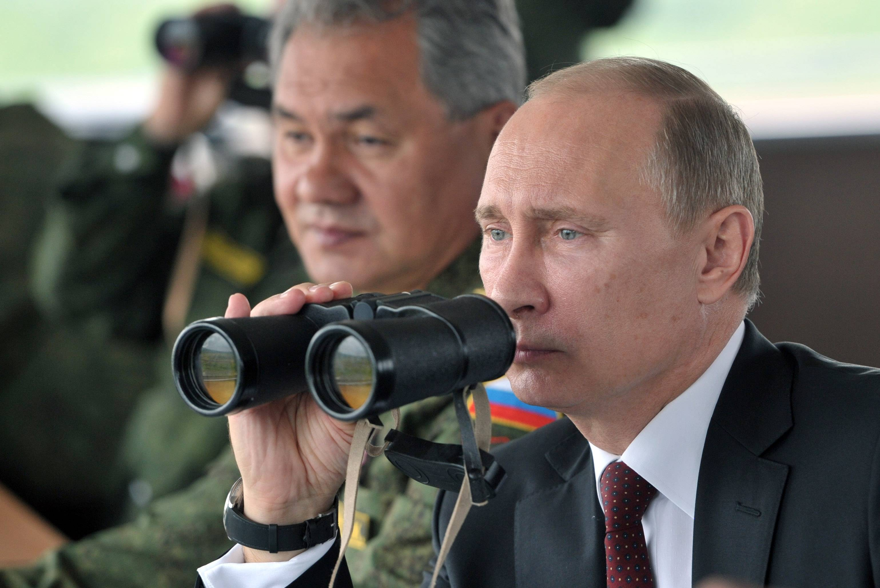 Russian President Vladimir Putin, flanked by Defense Minister Sergei Shoigu, uses binocular as he watches military exercises last July. In response to the turmoil in Ukraine, Putin on Wednesday ordered massive exercises involving most of its military units in western Russia amid tensions in Ukraine.