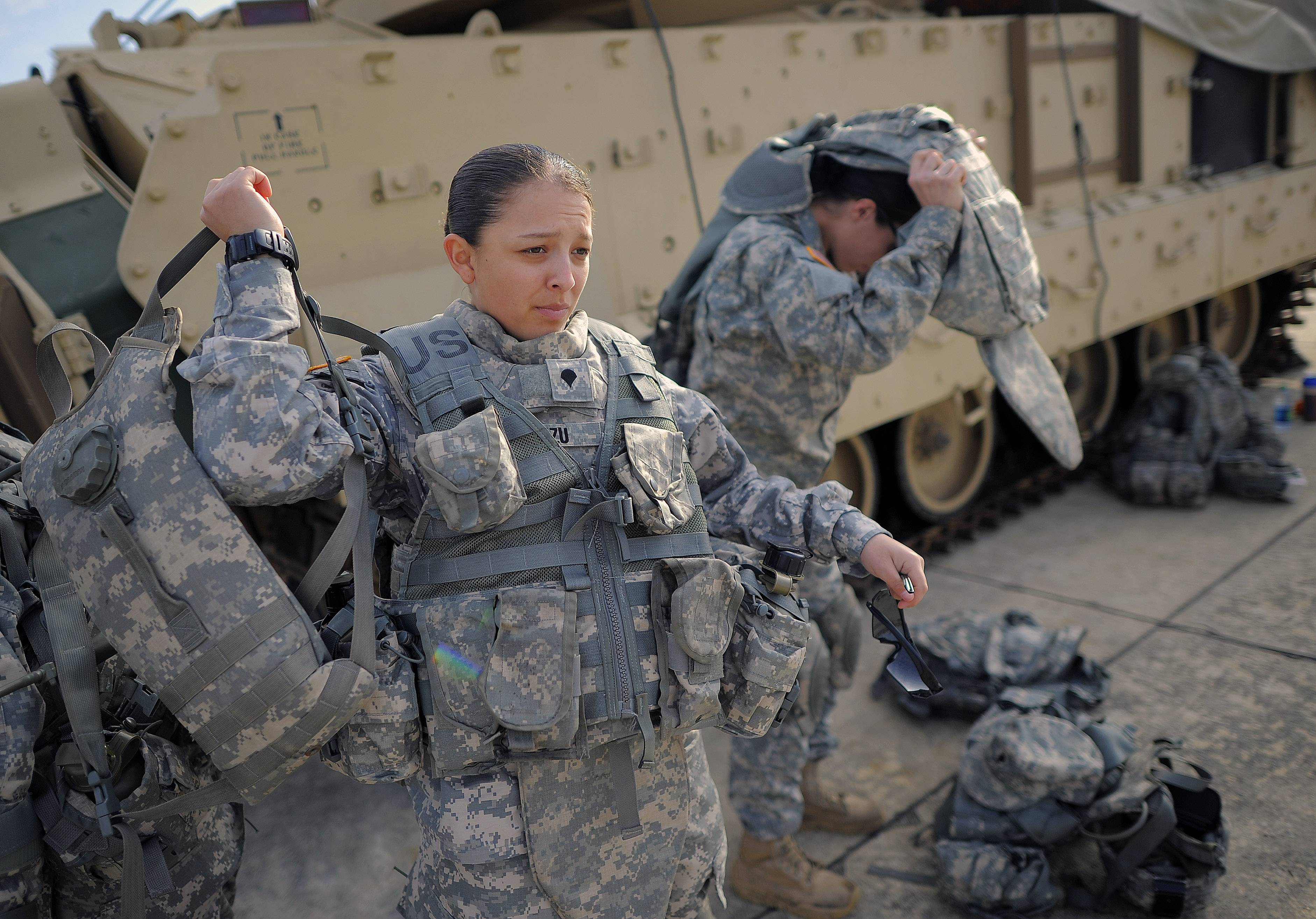 Spc. Karen Arvizu, left, puts on her hydration pack as part of an Army study to determine how all soldiers, including women, will be deemed fit to join its fighting units.