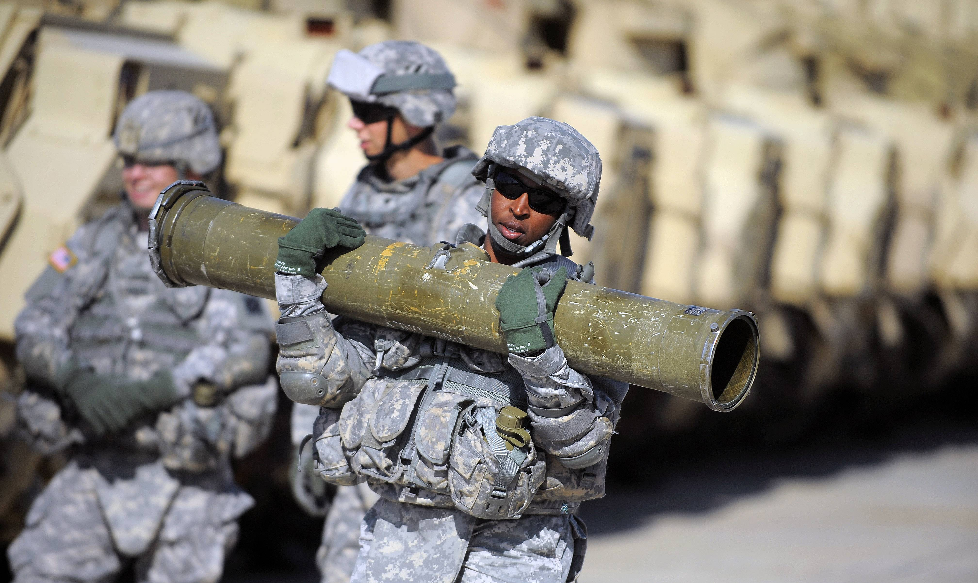 U.S. Army Corp. Jacqueline Beachum carries a 65-pound T.O.W. missile several yards before loading the dummy missile to the launcher of a Bradley Fighting Vehicle.