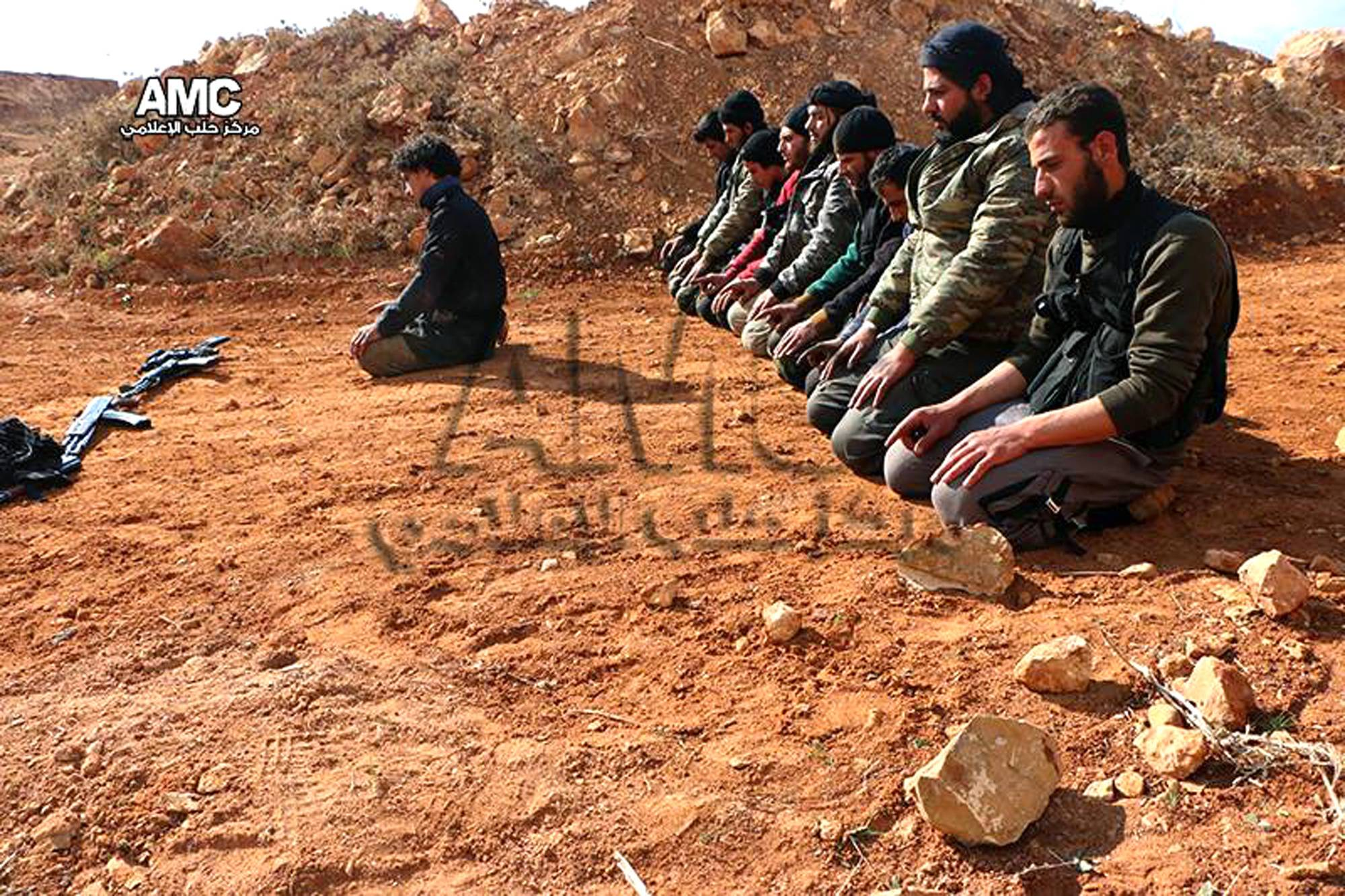 In this photo taken on Tuesday Feb. 25, 2014, this photo provided by the anti-government activist group Aleppo Media Center (AMC), which has been authenticated based on its contents and other AP reporting, shows Syrian rebels praying at the frontline of Sheikh Najjar village, in Aleppo, Syria. Syrian state media say troops have killed scores of al-Qaida-affiliated rebels in an ambush near the capital, Damascus.