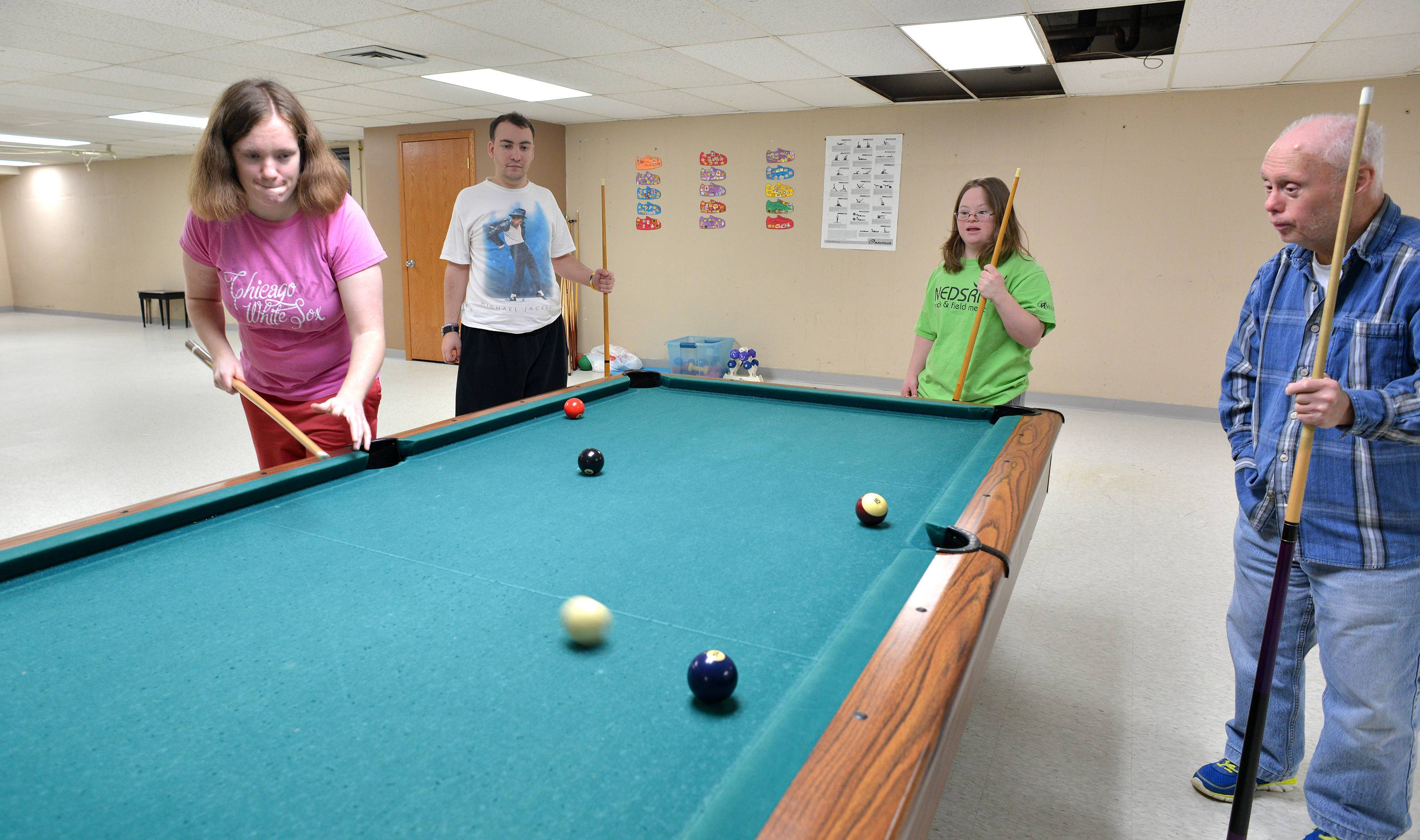 A large multipurpose room in the Deicke Home's basement offers several recreational opportunities. From left, residents Sarah Guidolin, Joe Passaretti, Katie Prentice and Raymond Maramba enjoy a game of pool.