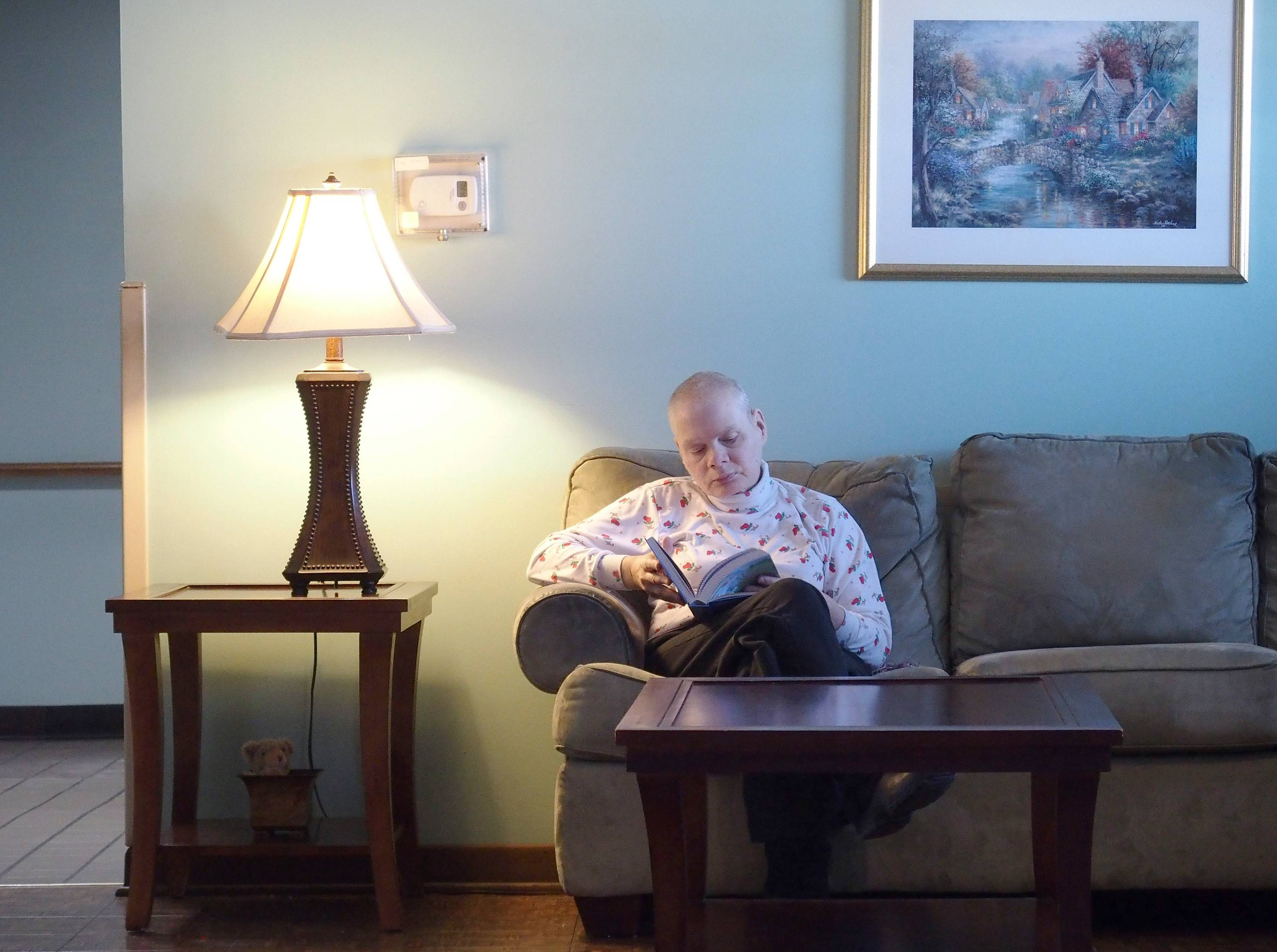 Resident Sherry Ubert, who has lived at the Deicke Home in Lombard for 30 years, spends some quiet time alone with her Bible in the home's living room.