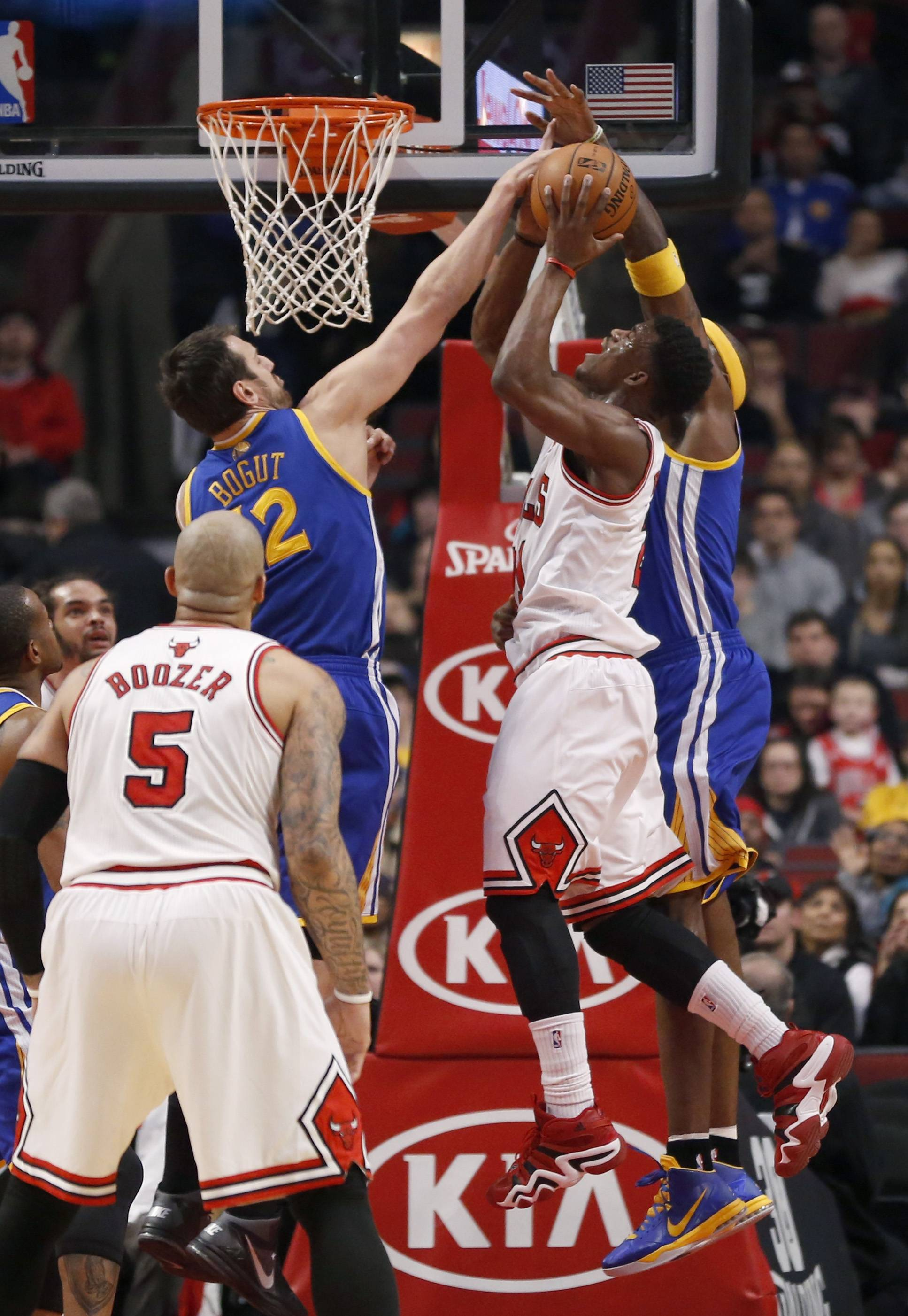 Chicago Bulls shooting guard Jimmy Butler (21) is fouled by Golden State Warriors center Jermaine O'Neal, right, as Andrew Bogut (12) also defends during the first half of an NBA basketball game, Wednesday, Feb. 26, 2014, in Chicago. Watching the play is Carlos Boozer (5).