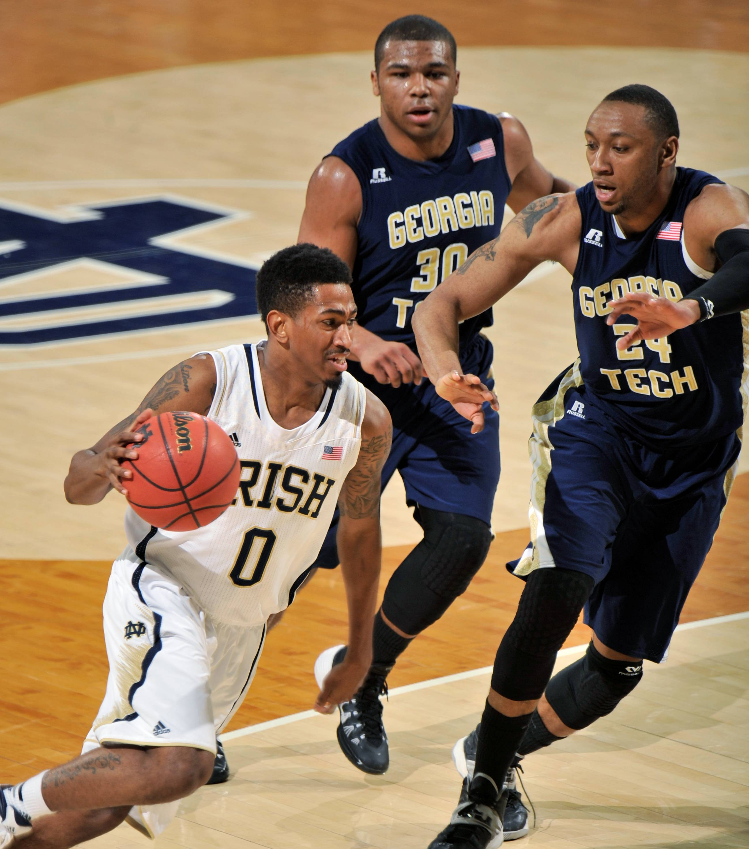 Notre Dame guard Eric Atkins, left, drives the lane as Georgia Tech guard Corey Heyward, middle, and Kammeon Holsey defend during the first half of an NCAA college basketball game, Wednesday, Feb. 26, 2014 in South Bend, Ind.